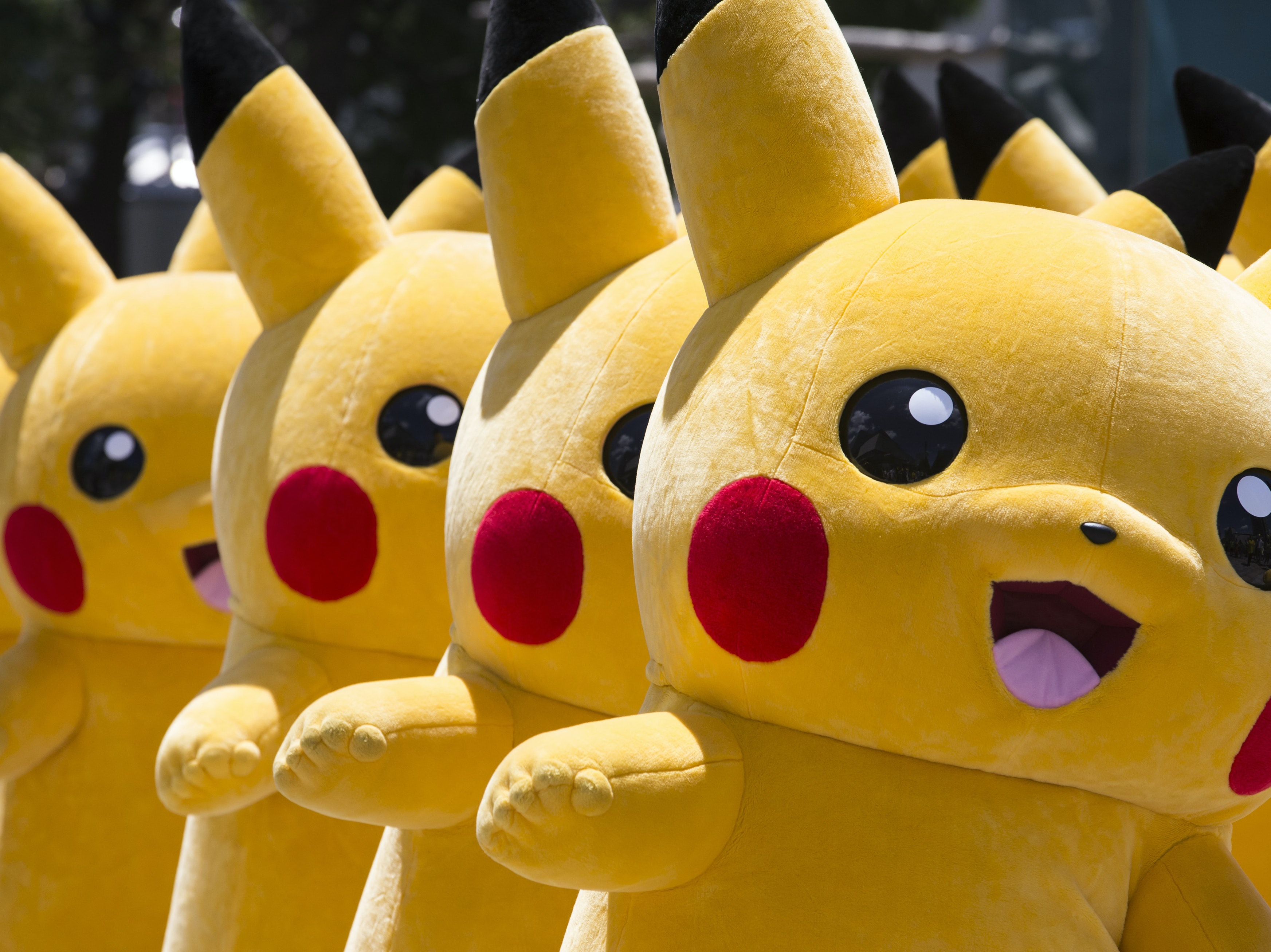 Performers dressed as Pikachu march during the Pikachu Outbreak event on August 7, 2016 in Yokohama, Japan.