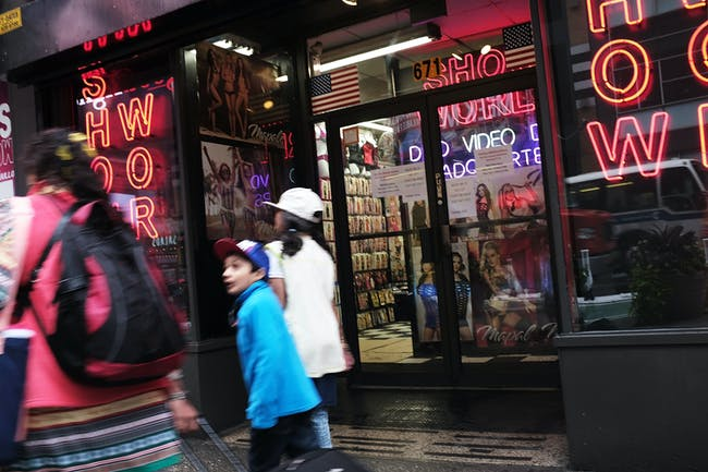 NEW YORK, NY - AUGUST 07: Pedestrians walk by one of the few remaining adult DVD stores in Times Square on August 7, 2017 in New York City. The owners of the city's remaining peep shows, adult DVD stores and strip clubs say a recent court ruling could put them out of business. The state Court of Appeals has reinstated rules that date to 2001 forbidding any business with 'live performances characterized by an emphasis on certain specified anatomical areas or specified sexual activities, as well as sexually explicit videos from all but a few selected city zones. Once home to dozens of peep shows and pornography cinemas, only a few now survive following a crack down that started with former Mayor Rudy Giuliani and his effort to clean-up Times Square in the 1990s. (Photo by Spencer Platt/Getty Images)