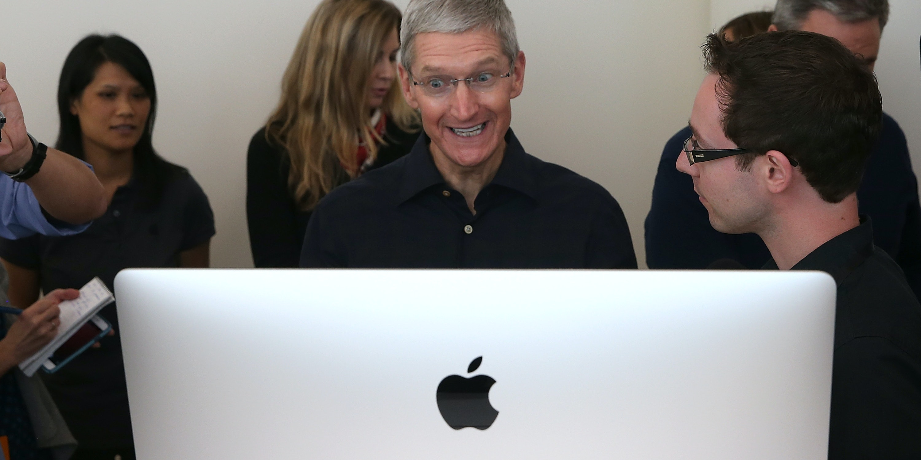 Apple CEO Tim Cook looks at the new 27 inch iMac during an Apple special event on October 16, 2014 in Cupertino, California.