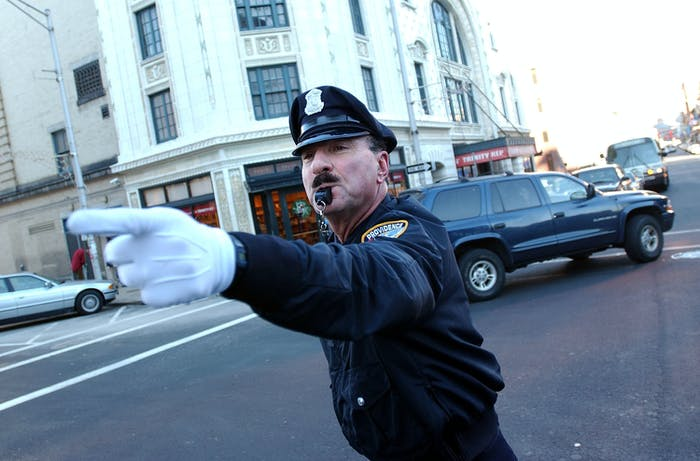 PROVIDENCE, RI - DECEMBER 14: Retired police officer Tony Lepore performs his dance routine while directing traffic December 14, 2004 in downtown Providence, Rhode Island. Lepore has been entertaining drivers and directing traffic at intersections around Providence for 20 years. He came upon the idea after seeing a 'Candid Camera' clip of New York City police officers who flamboyantly directed traffic in the 1950's. (Photo by Darren McCollester/Getty Images)