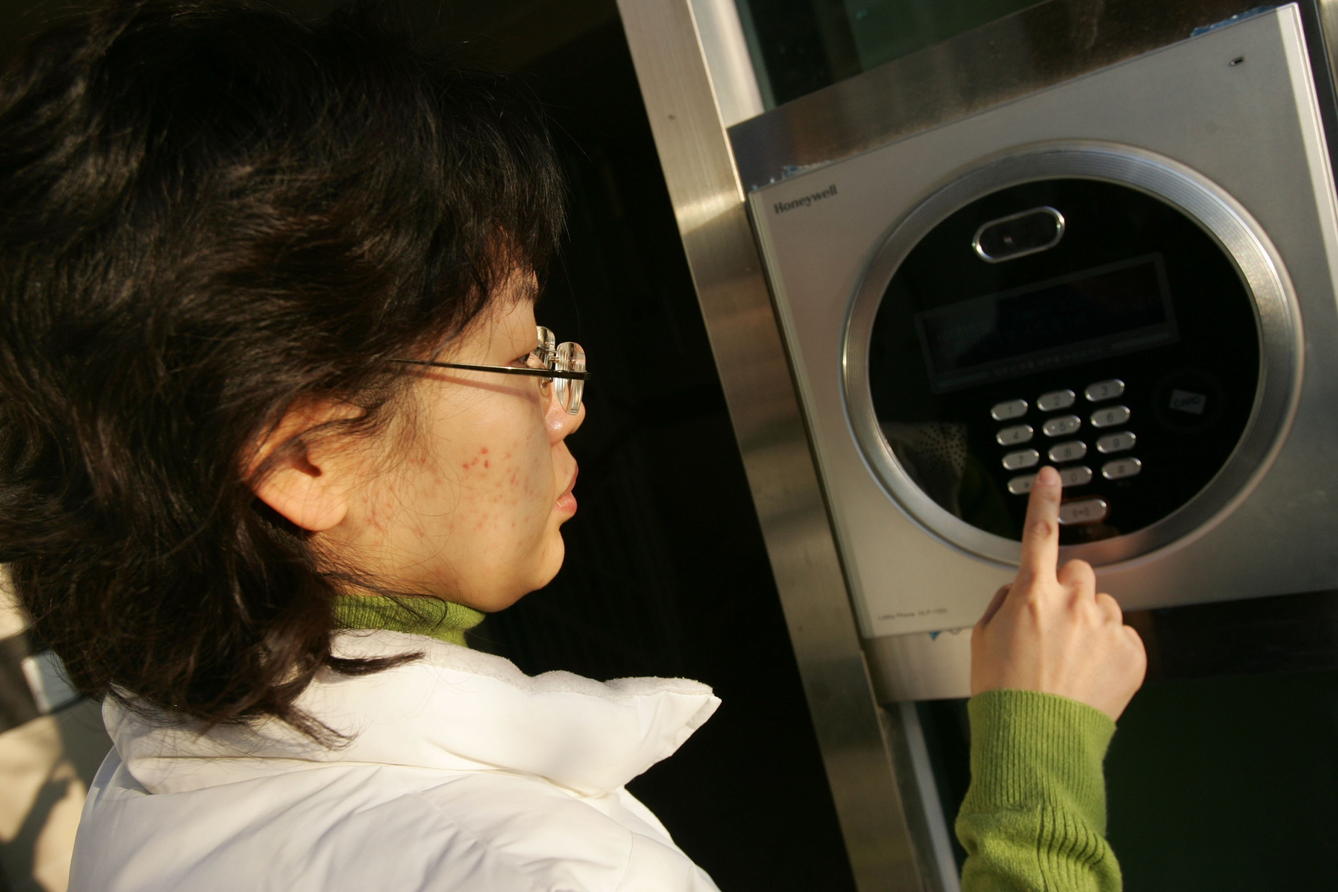 A resident uses a keypad to enter her home at the smart home town complex (Home Network) on November 29, 2006 in Incheon, South Korea.