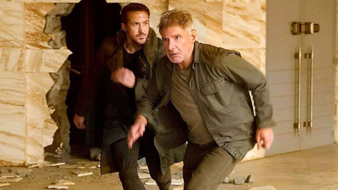 Deckard runs from an explosion with Officer K.