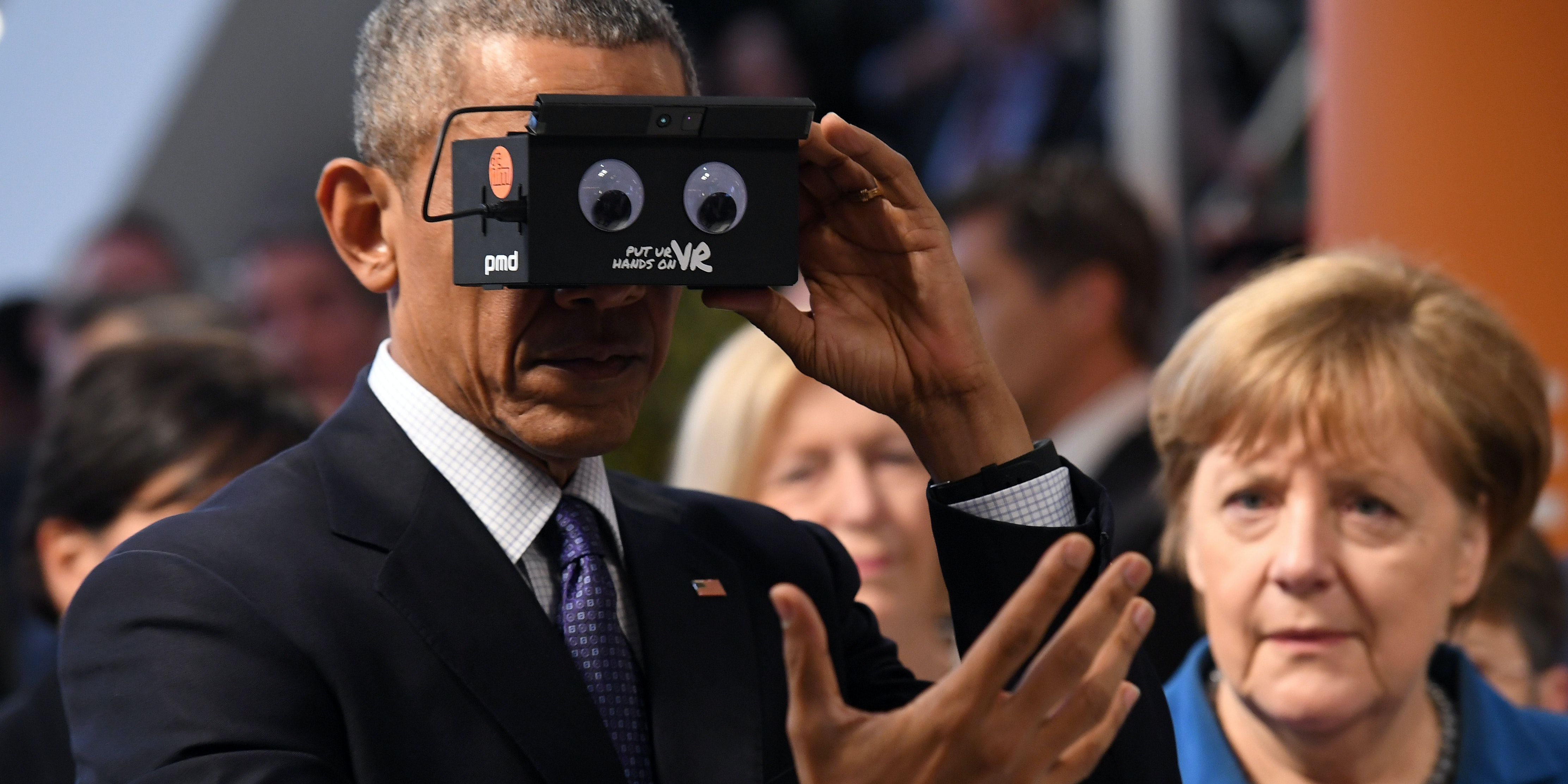 HANOVER, GERMANY - APRIL 25:  U.S. President Barack Obama and German Chancellor Angela Merkel test virtual reality glasses at the ifm electronics stand at the Hannover Messe industrial trade fair on April 25, 2016 in Hanover, Germany. This is likely Obama's last trip to Germany as U.S. president. The Hannover Messe is the world's largest industrial trade fair.  (Photo by Alexander Koerner/Getty Images)
