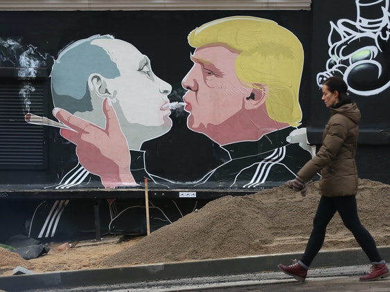 A woman walks past a mural showing U.S. President-elect Donald Trump (R) blowing marijuana smoke into the mouth of Russian President Vladimir Putin on the wall of a bar-b-que restaurant on November 23, 2016 in Vilnius, Lithuania. Many people in the three Baltic nations of Lithuania, Latvia and Estonia are concerned that Russia, because Trump has expressed both admiration for Putin and doubt over defending NATO member states, will be emboldened to intervene militarily in the Baltics.