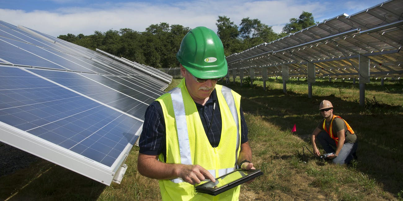Worker maintaining solar panels of Long Island Solar Farm