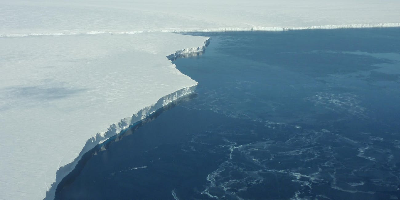 The vertical face of the ice shelf is almost 200 feet high and is estimated to extend another 1000 feet below the ocean surface. This photo was taken from NASA's DC-8 flying science laboratory during an IceBridge mission flight.