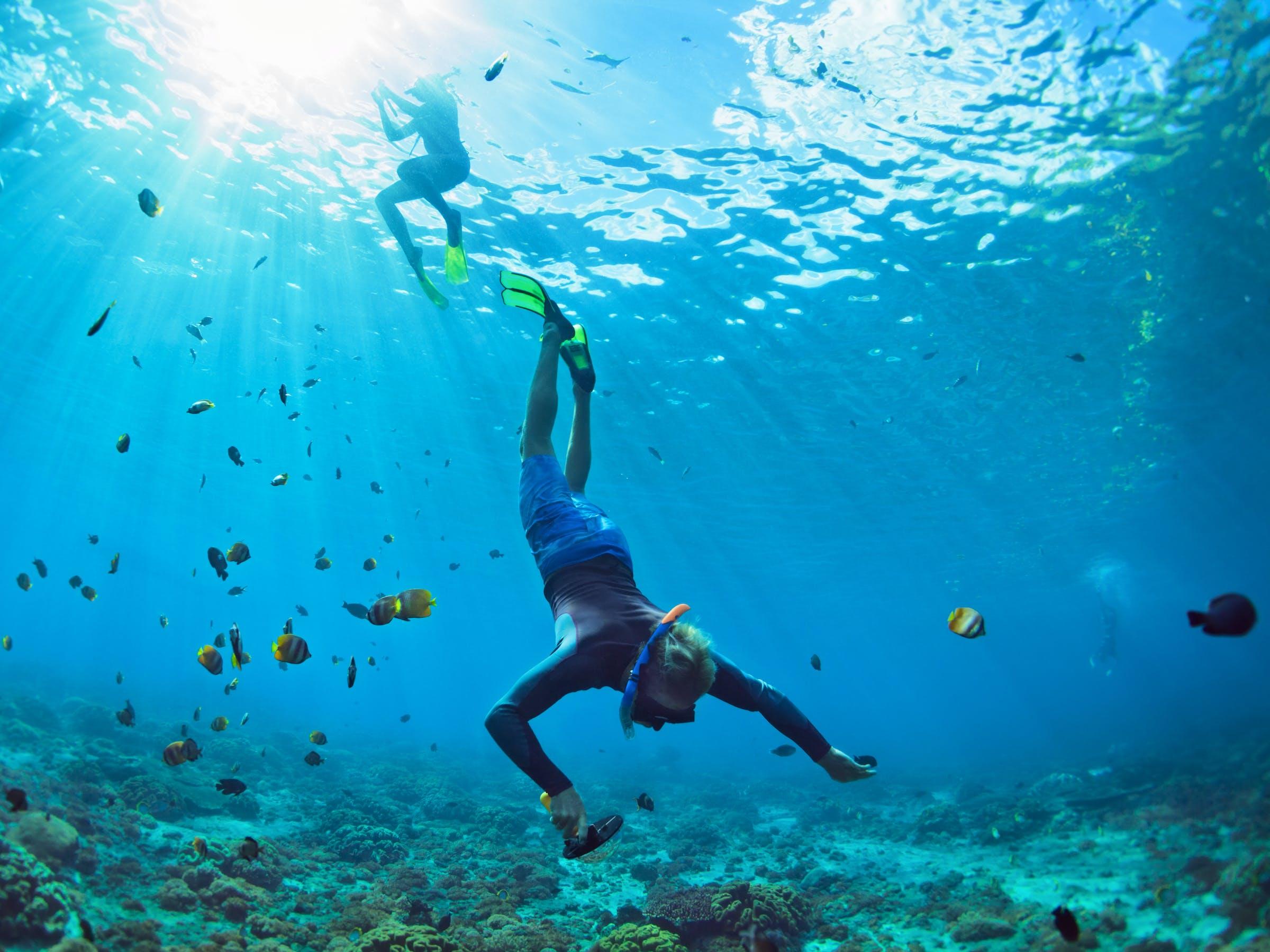 man snorkeling in tropical ocean