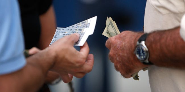 A fan holds tickets and another holds money before the Philadelphia Phillies take on the Tampa Bay Rays during game one of the 2008 MLB World Series on October 22, 2008 at Tropicana Field in St. Petersburg, Florida.