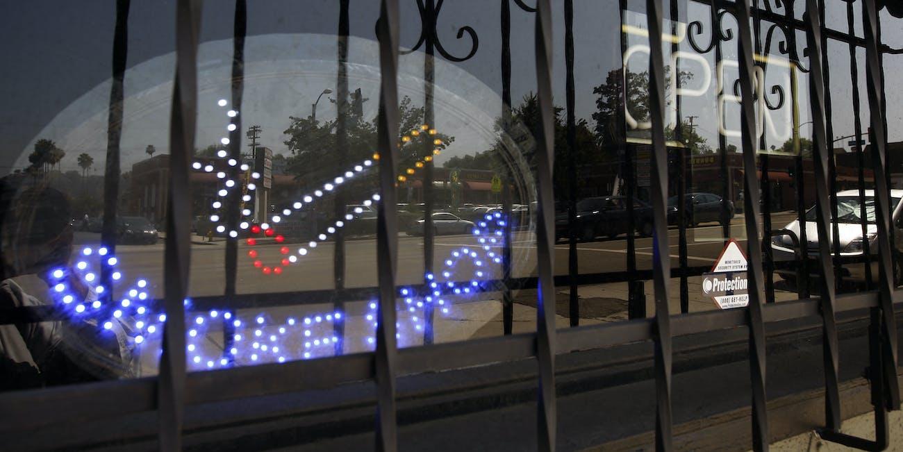 weed pot marijuana dispensary safe neighborhood smoke shop colorado los angeles urban economics cigarette open sign neon