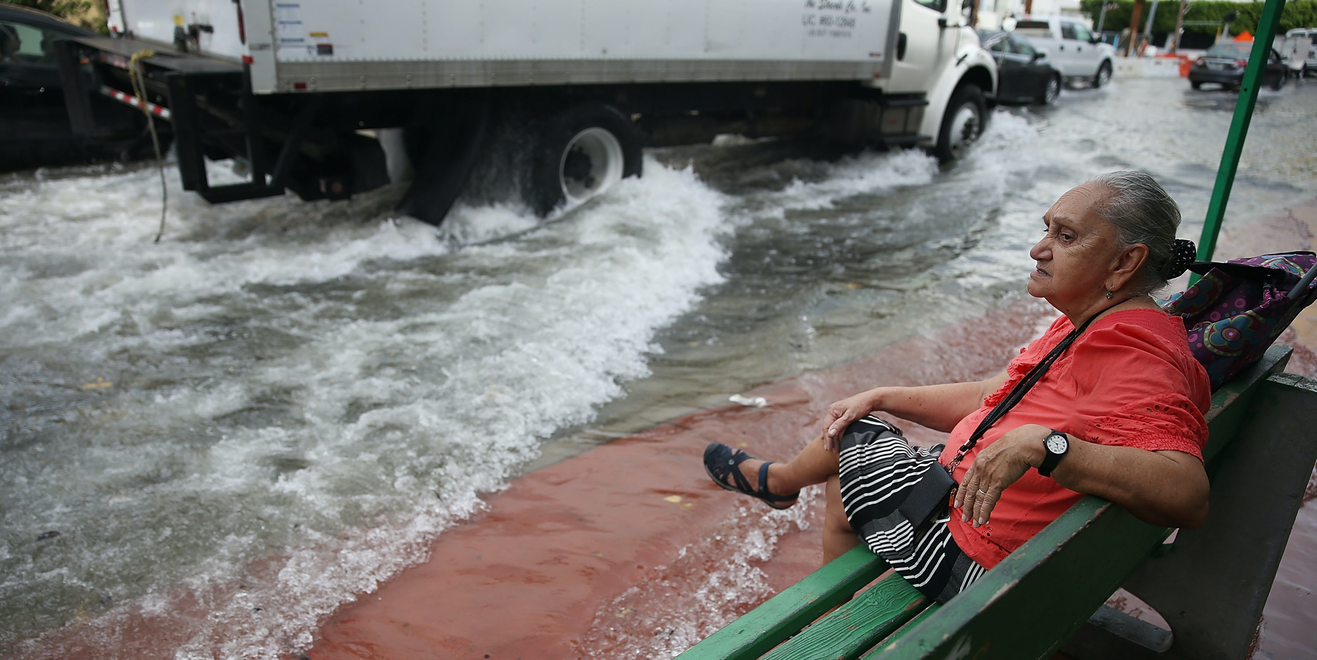 MIAMI BEACH, FL - SEPTEMBER 29:  Mayabel Rents waits for a bus next to a flooded street that was caused by the combination of the lunar orbit which caused seasonal high tides and what many believe is the rising sea levels due to climate change on September 29, 2015 in Miami Beach, Florida. The City of Miami Beach is in the middle of a five-year, $400 million storm water pump program and other projects that city officials hope will keep the ocean waters from inundating the city as the oceans rise even more in the future.  (Photo by Joe Raedle/Getty Images)