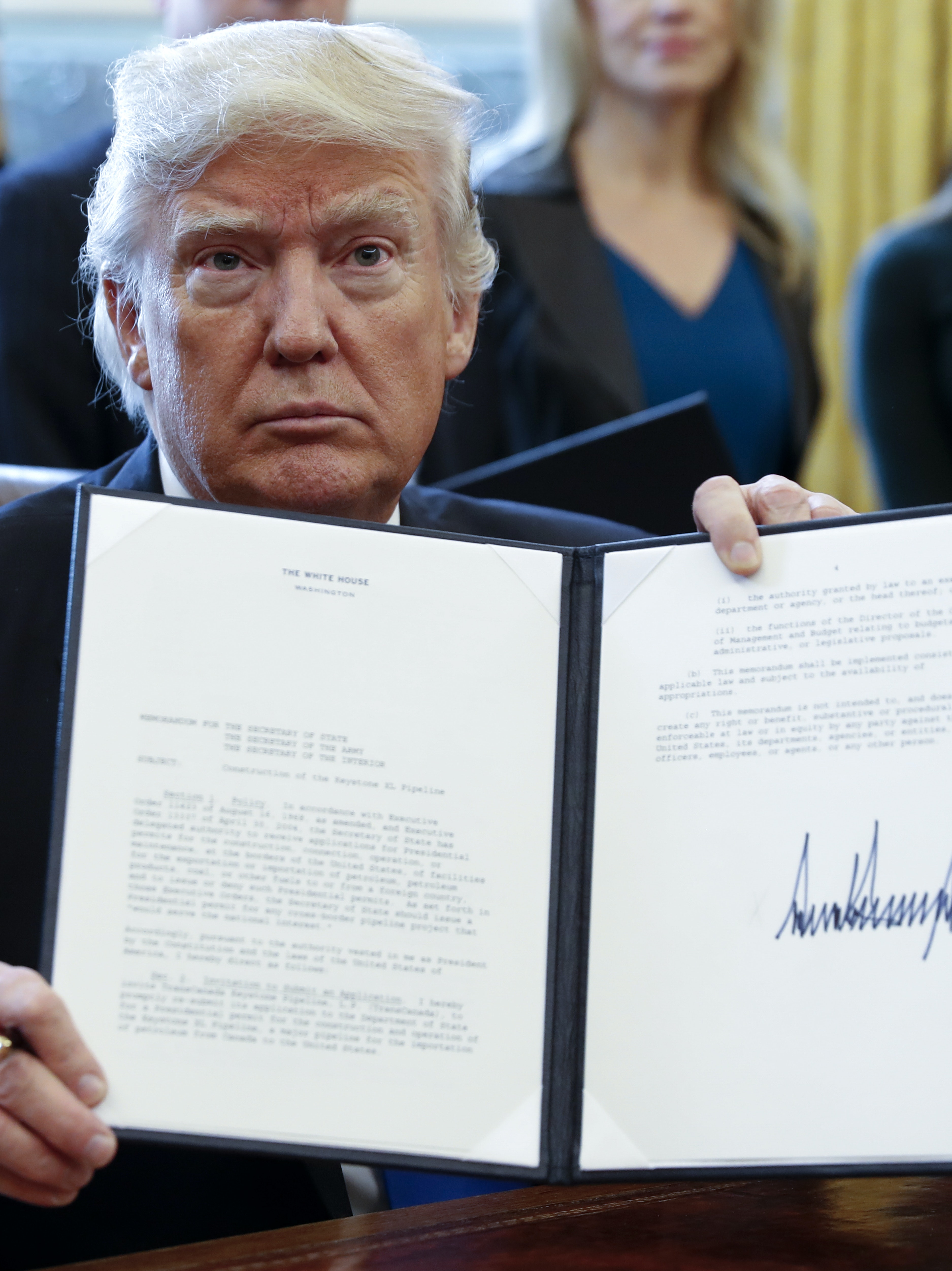WASHINGTON, DC - JANUARY 24: US President Donald Trump displays one of five executive orders he signed related to the oil pipeline industry in the oval office of the White House January 24, 2017 in Washington, DC. President Trump has a full day of meetings including one with Senate Majority Leader Mitch McConnell and another with the full Senate leadership. (Photo by Shawn Thew-Pool/Getty Images)