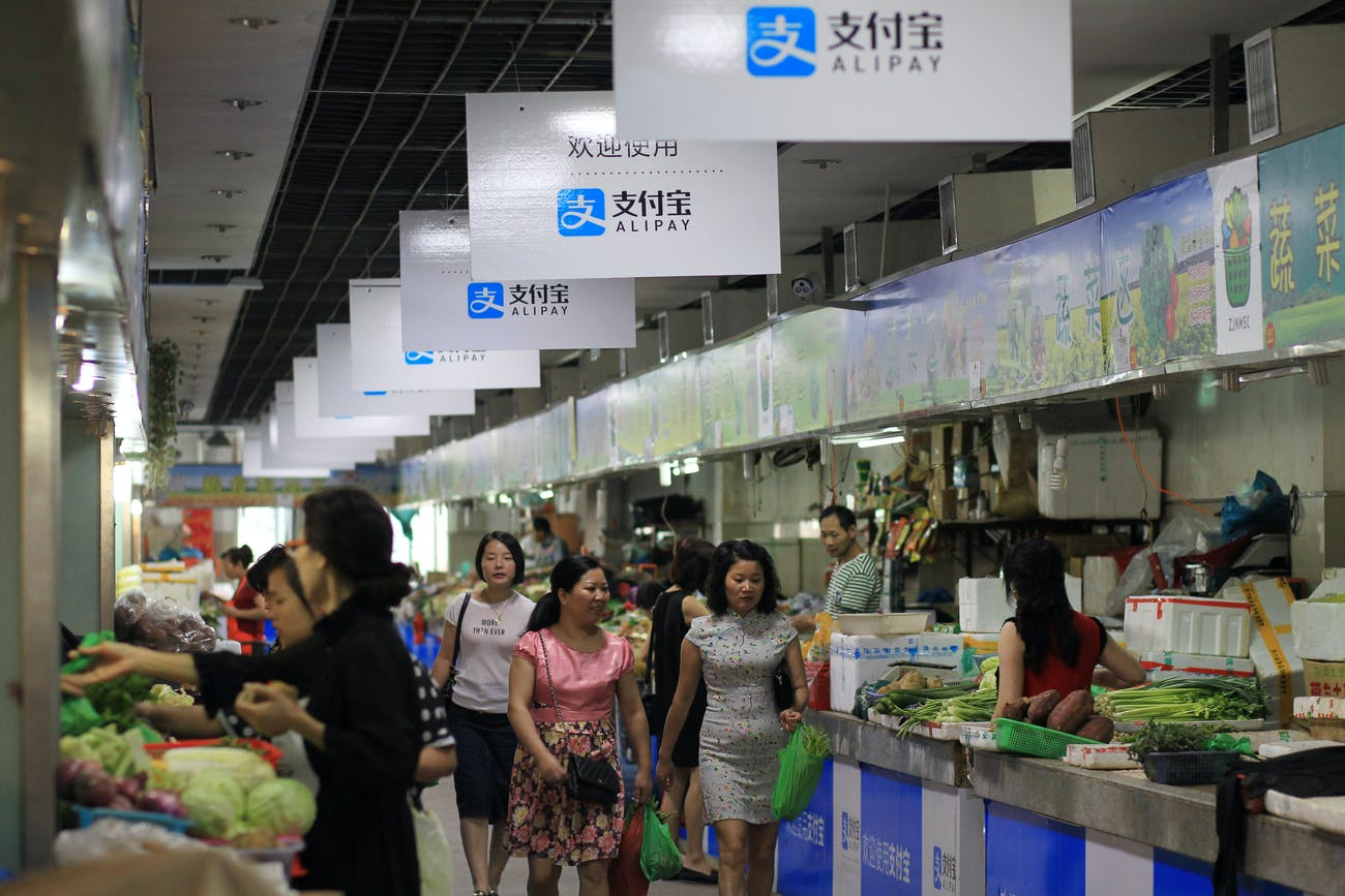 WENZHOU, CHINA - SEPTEMBER 14: (CHINA OUT) Consumers purchase at a local market with boards of Alipay hung up on September 14, 2015 in Wenzhou, Zhejiang Province of China. Over 70 stalls in a local market started to use Alipay, a popular online payment service in China, to receive money from consumers. Consumers scan the QR to pay for their purchase in the WiFi covered market in Wenzhou. (Photo by VCG/VCG via Getty Images)