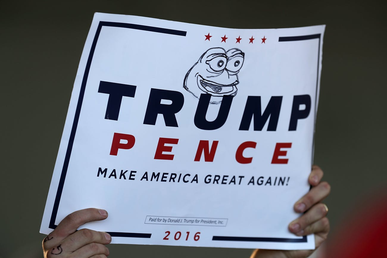 MINNEAPOLIS, MN - NOVEMBER 06: A supporter holds a campaign sign for Republican presidential nominee Donald Trump with 'Pepe the Frog' drawn on it during a rally in the Sun Country Airlines Hangar at MinneapolisÐSaint Paul International Airport November 6, 2016 in Minneapolis, Minnesota. With less than 48 hours until Election Day in the United States, Trump and his opponent, Democratic presidential nominee Hillary Clinton, are campaigning in key battleground states that each must win to take the White House. (Photo by Chip Somodevilla/Getty Images)