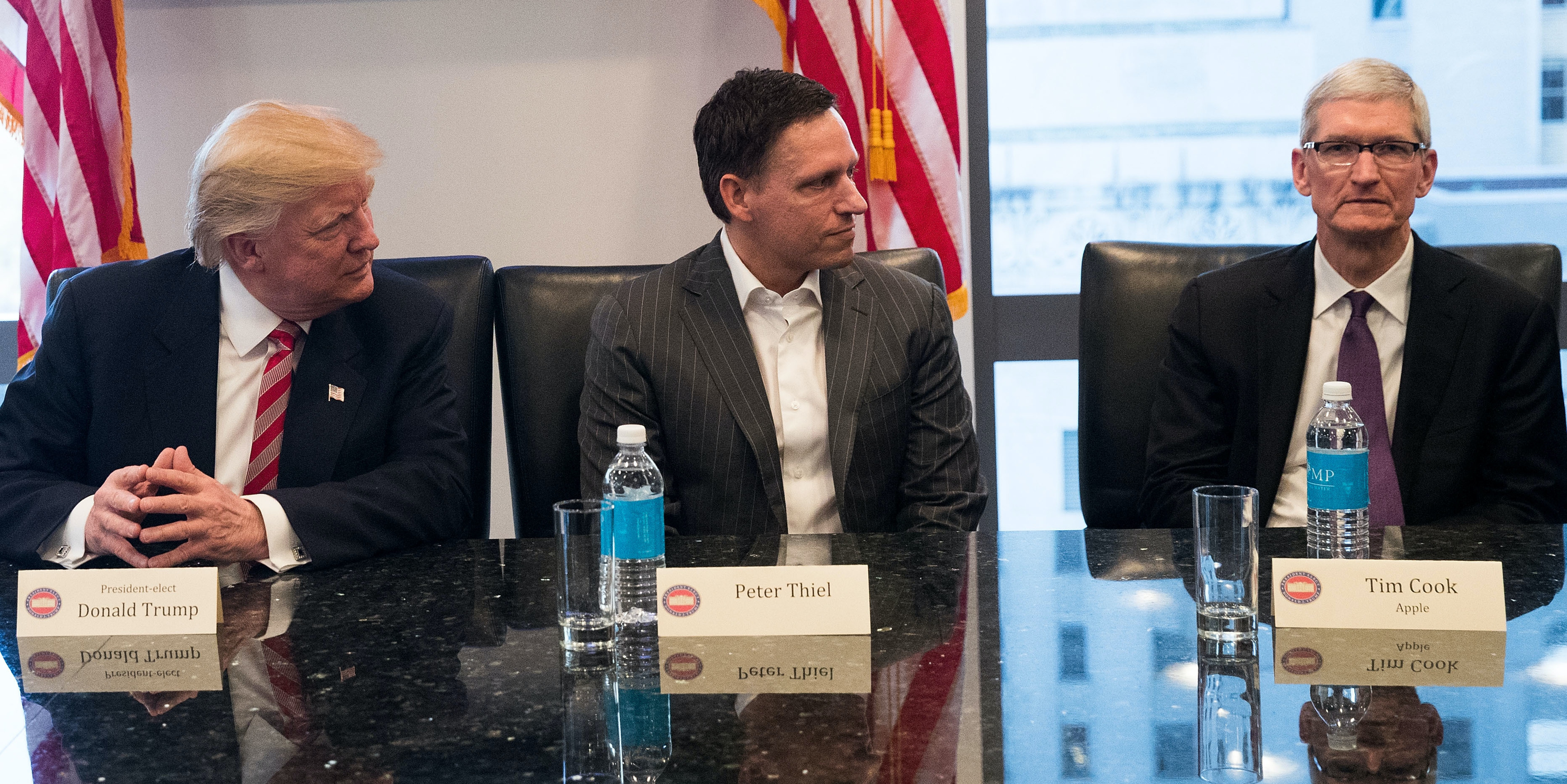 NEW YORK, NY - DECEMBER 14: (L to R) President-elect Donald Trump, Peter Thiel and Tim Cook, chief executive officer of Apple, Inc., listen during a meeting with technology executives at Trump Tower, December 14, 2016 in New York City. This is the first major meeting between President-elect Trump and technology industry leaders. (Photo by Drew Angerer/Getty Images)
