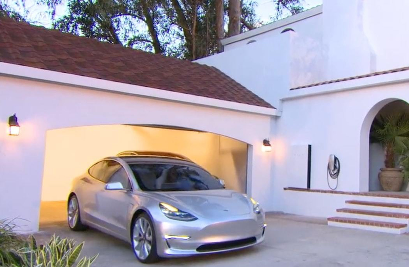 A Tesla Model 3, pulling out of a garage with solar panels on the roof.