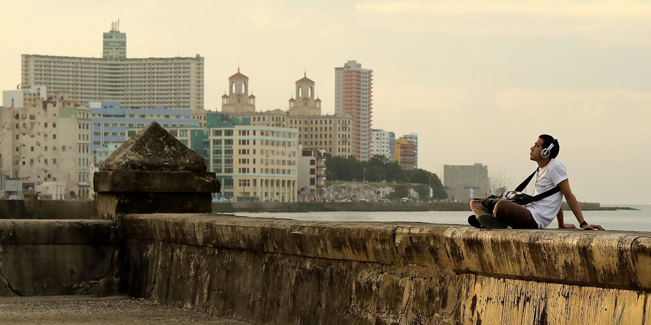 HAVANA, CUBA - DECEMBER 06: A man listens to music while sitting on the seawall along the famous Malecon as daily life resumes in the capital city following a nine-day mouring period after the death of revolutionary leader December 6, 2016 in Havana, Cuba. Castro, who died November 25 at the age of 90, was entombed Sunday in the the Cementerio Santa Ifigenia in Santiago de Cuba. (Photo by Chip Somodevilla/Getty Images)