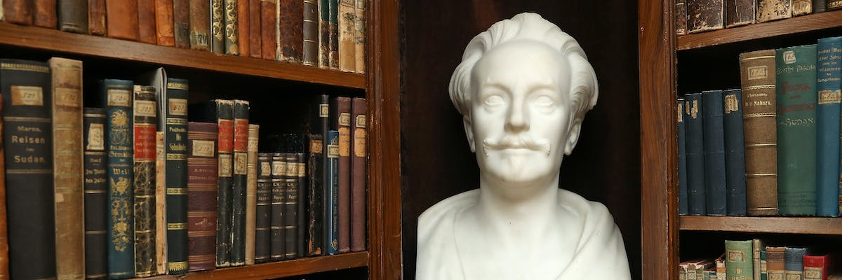 RADEBEUL, GERMANY - FEBRUARY 22:  A bust of 19th-century German writer Karl May stands among travel guides and accounts that served May with inspiration in the original, furnished library in the Karl May Museum, May's former residence, on February 22, 2017 in Radebeul, Germany. May's Wild West series, with its protaganists of Old Shatterhand and Winnetou, is an indelible facet of central European childhood literature and has sold millions of copies worldwide. May was born on February 25, 1842 and his 175th birthday occurs this coming Saturday.  (Photo by Sean Gallup/Getty Images)