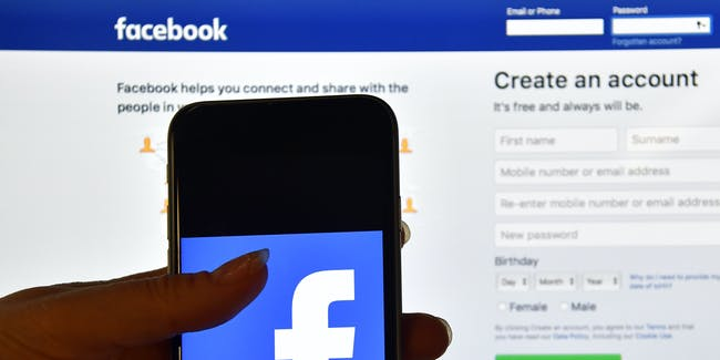 LONDON, ENGLAND - AUGUST 03: A person holds an iPhone displaying the Facebook app logo in front of a computer screen showing the facebook login page on August 3, 2016 in London, England. (Photo by Carl Court/Getty Images)