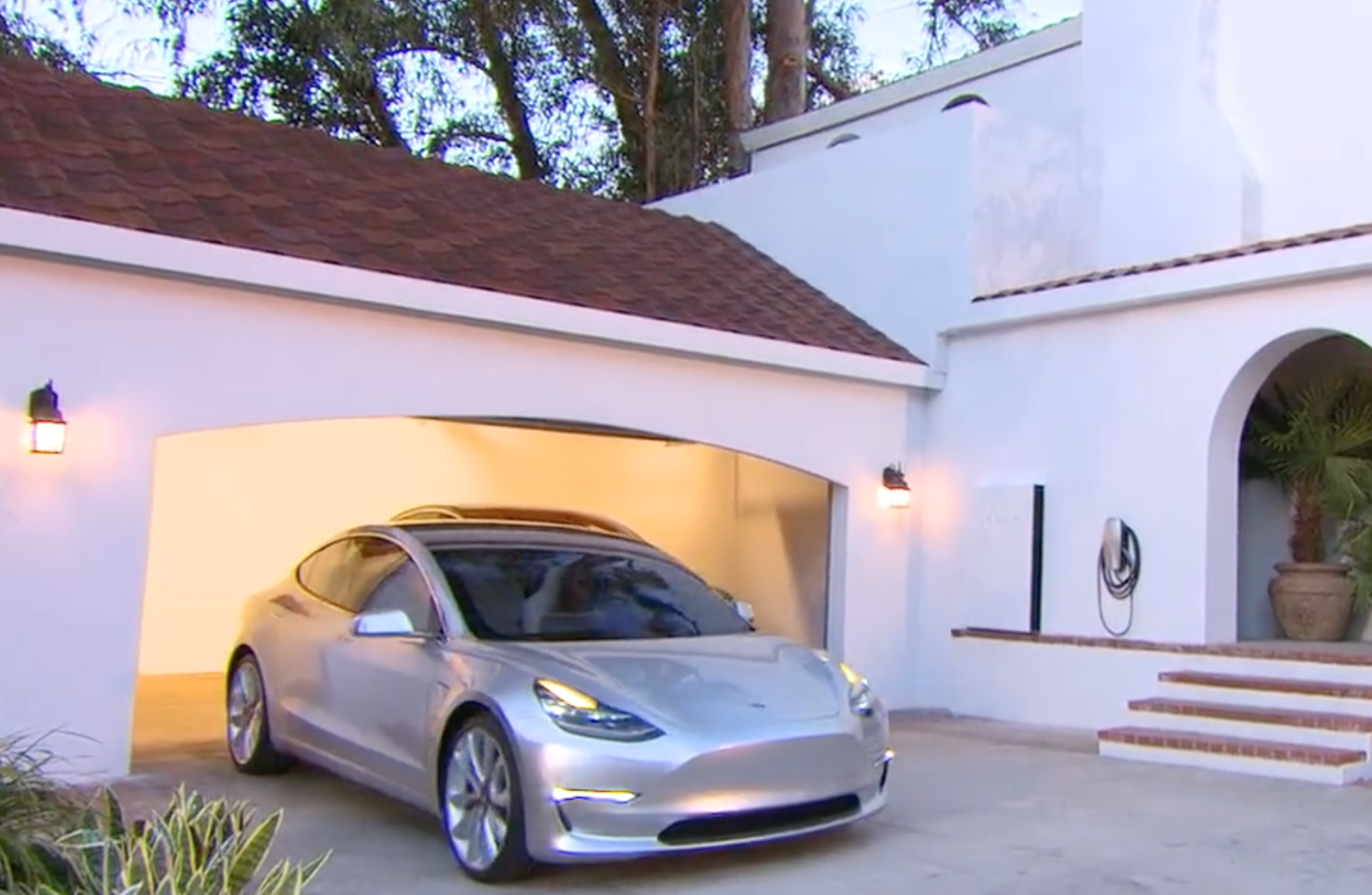 A Tesla Model 3 rolls out of a garage on a home that has solar panels in an event on Friday night.