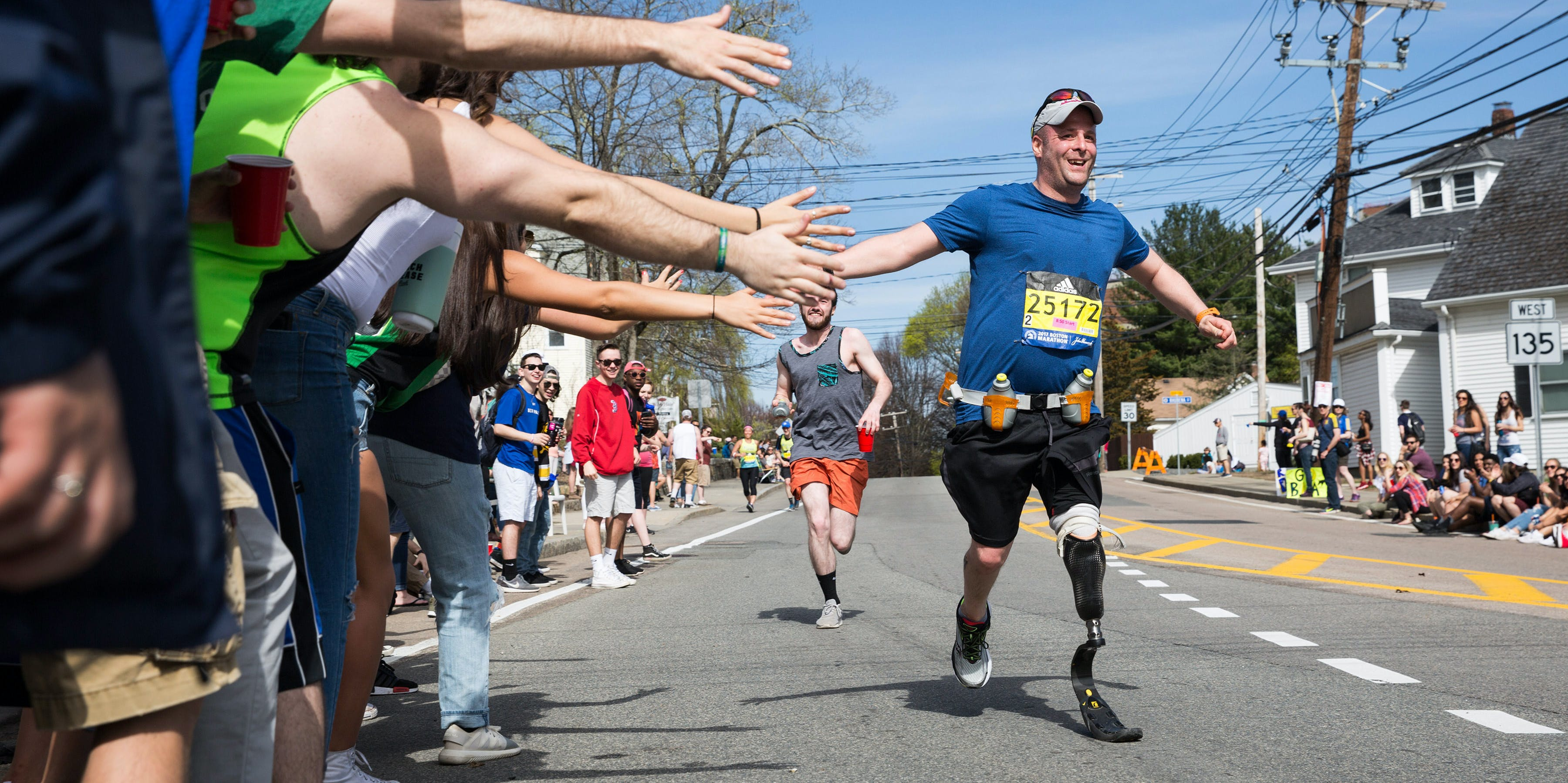 FRAMINGHAM, MA - APRIL 17: Spectators give high fives to a disabled runner as he makes his way past the 6 mile mark of the Boston Marathon on April 17, 2017 in Framingham, Massachusetts.  (Kayana Szymczak/Getty Images)