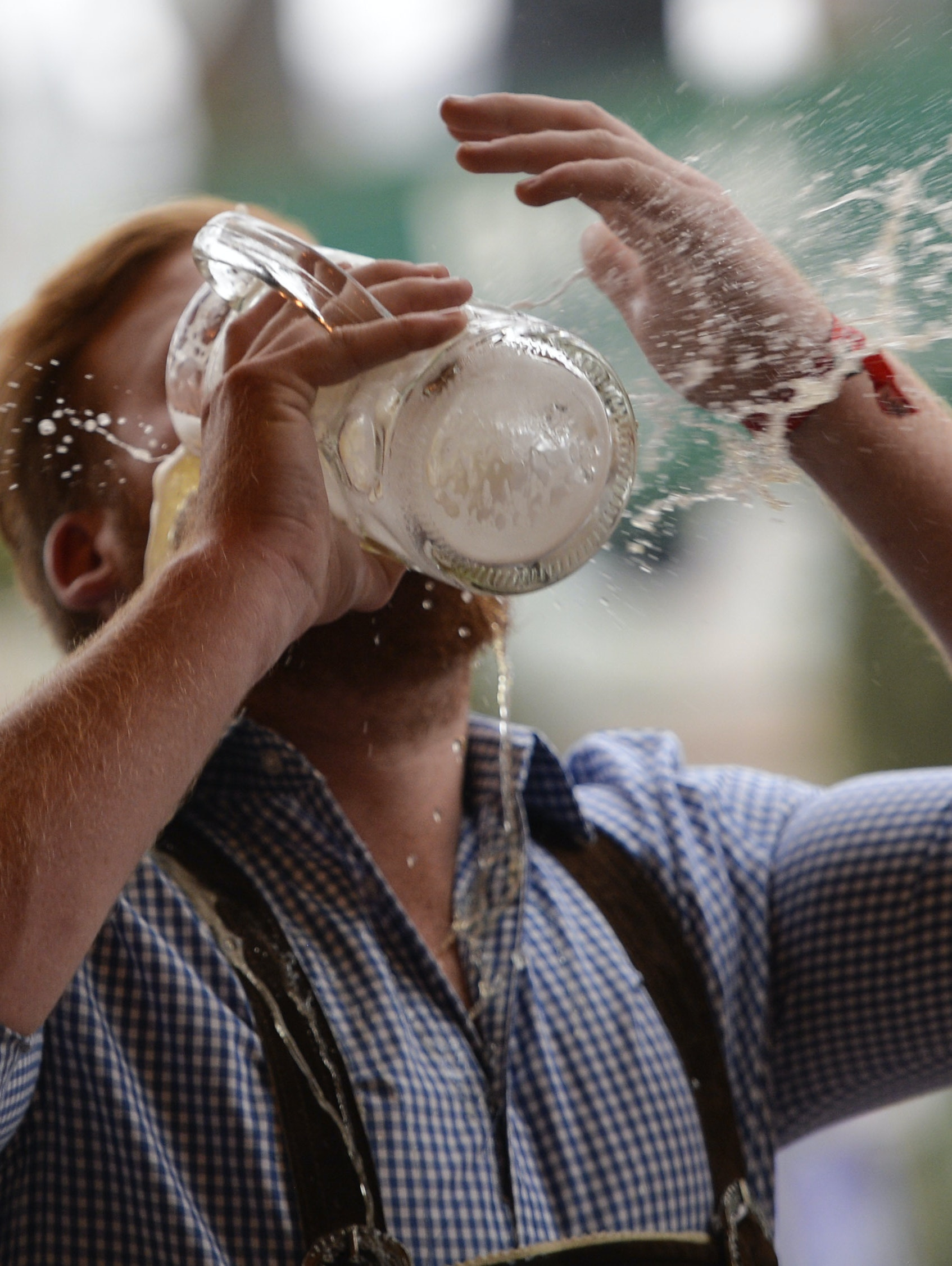 A reveller spills beer as he tries to empty his stein in one sitting at the Hofbraeu tent on the opening day of the 2015 Oktoberfest on September 19, 2015 in Munich, Germany.