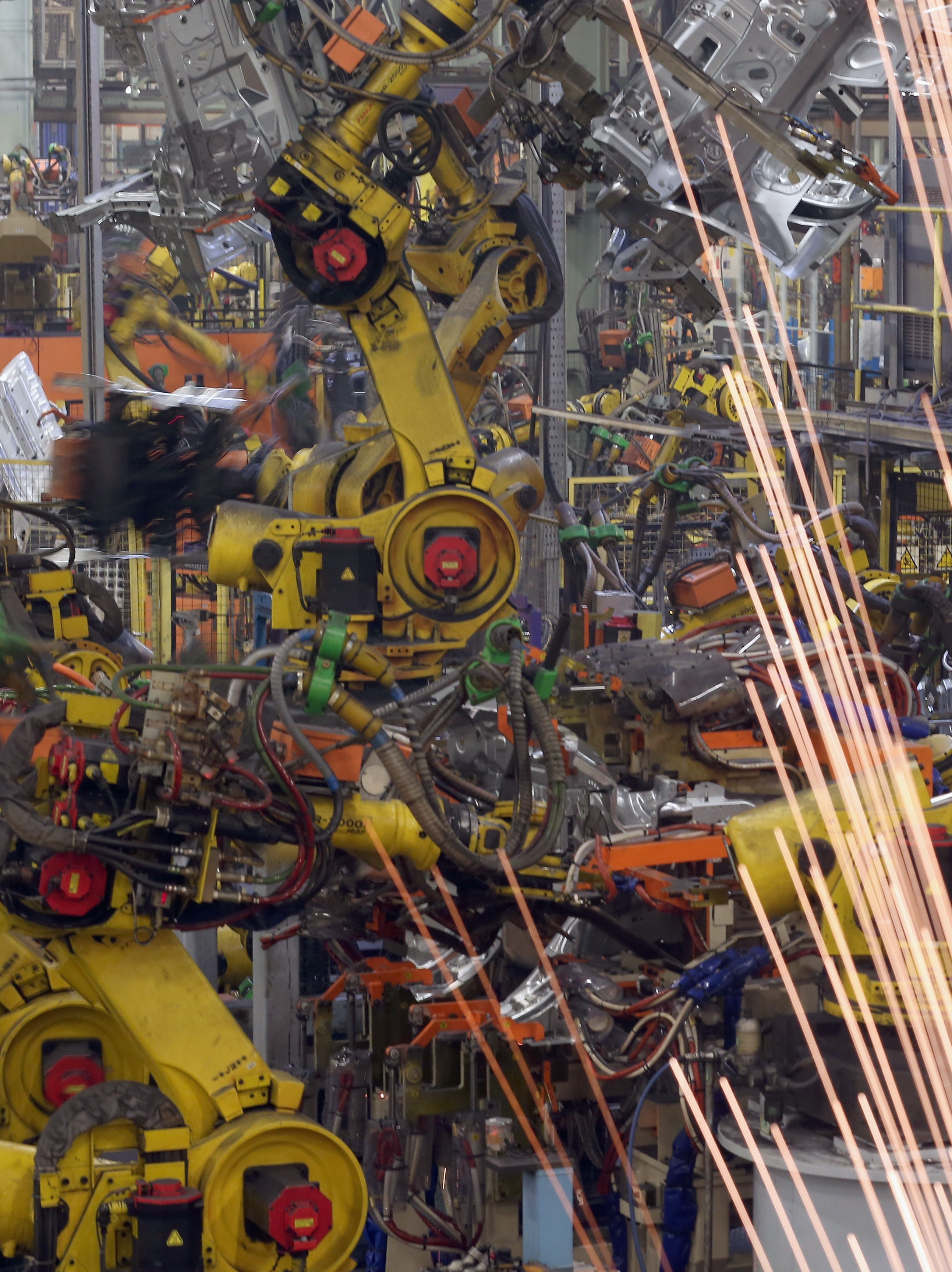 Robotic arms assemble and weld the body shell of a Nissan car on the production line at Nissan's Sunderland plant in England.