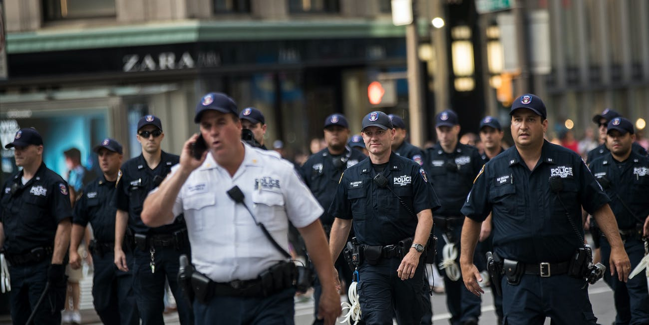NEW YORK, NY - AUGUST 13: New York City Police Officers (NYPD) move to remove protestors from the middle of the street on Fifth Avenue as they marched against white supremacy and racism, August 13, 2017 in New York City. 32-year-old Heather Heyer was killed in Charlottesville on Saturday when a car driven by a white supremacist barreled into a crowd of counter-protesters following violence at the Unite the Right rally. (Photo by Drew Angerer/Getty Images)