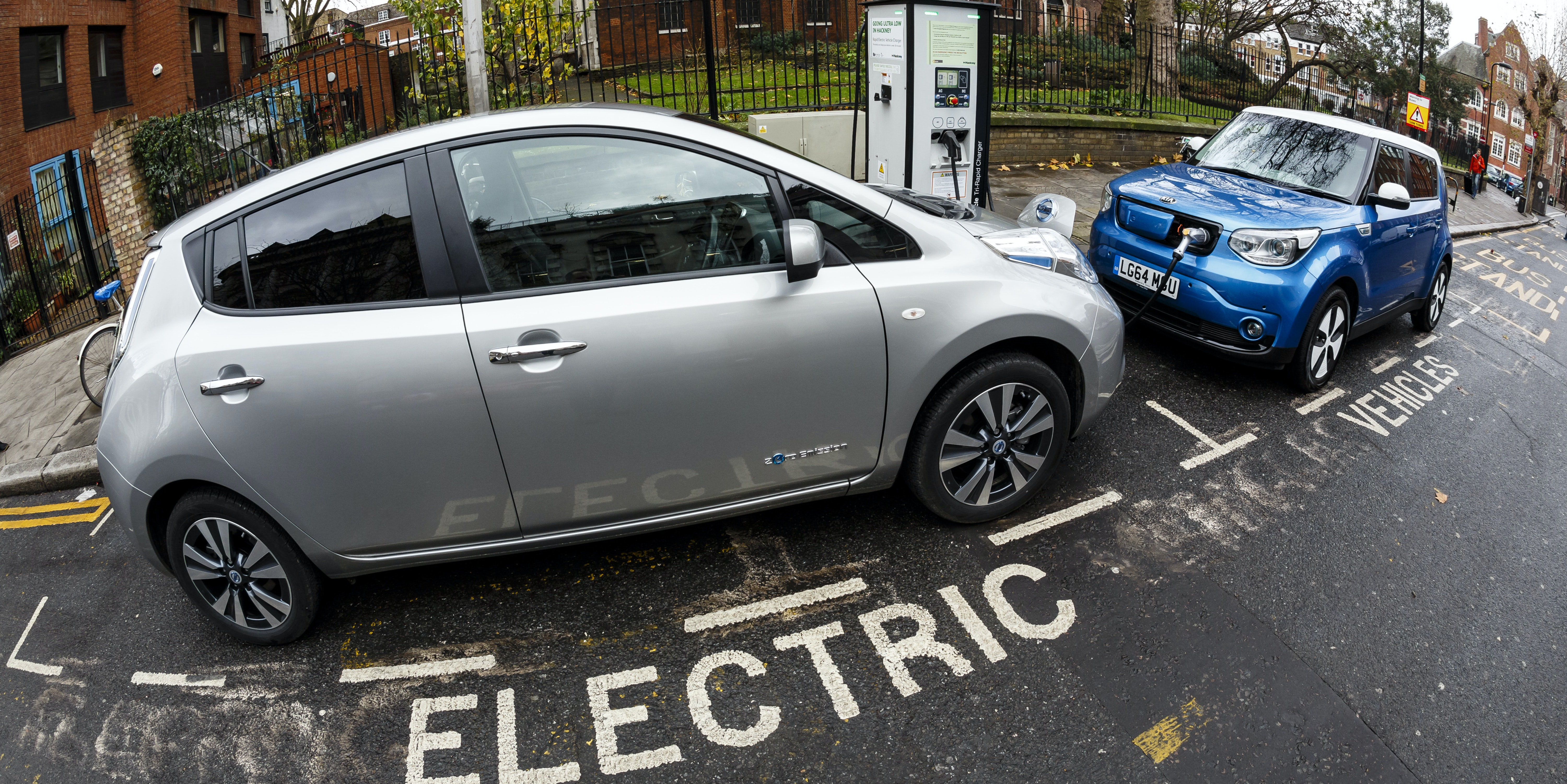 Go Ultra Low Nissan LEAF (L) and Kia Soul EV (R) on charge on a London street. Ultra-low emission vehicles such as this can cost as little as 2p per mile to run and some electric cars and vans have a range of up to 700 miles.