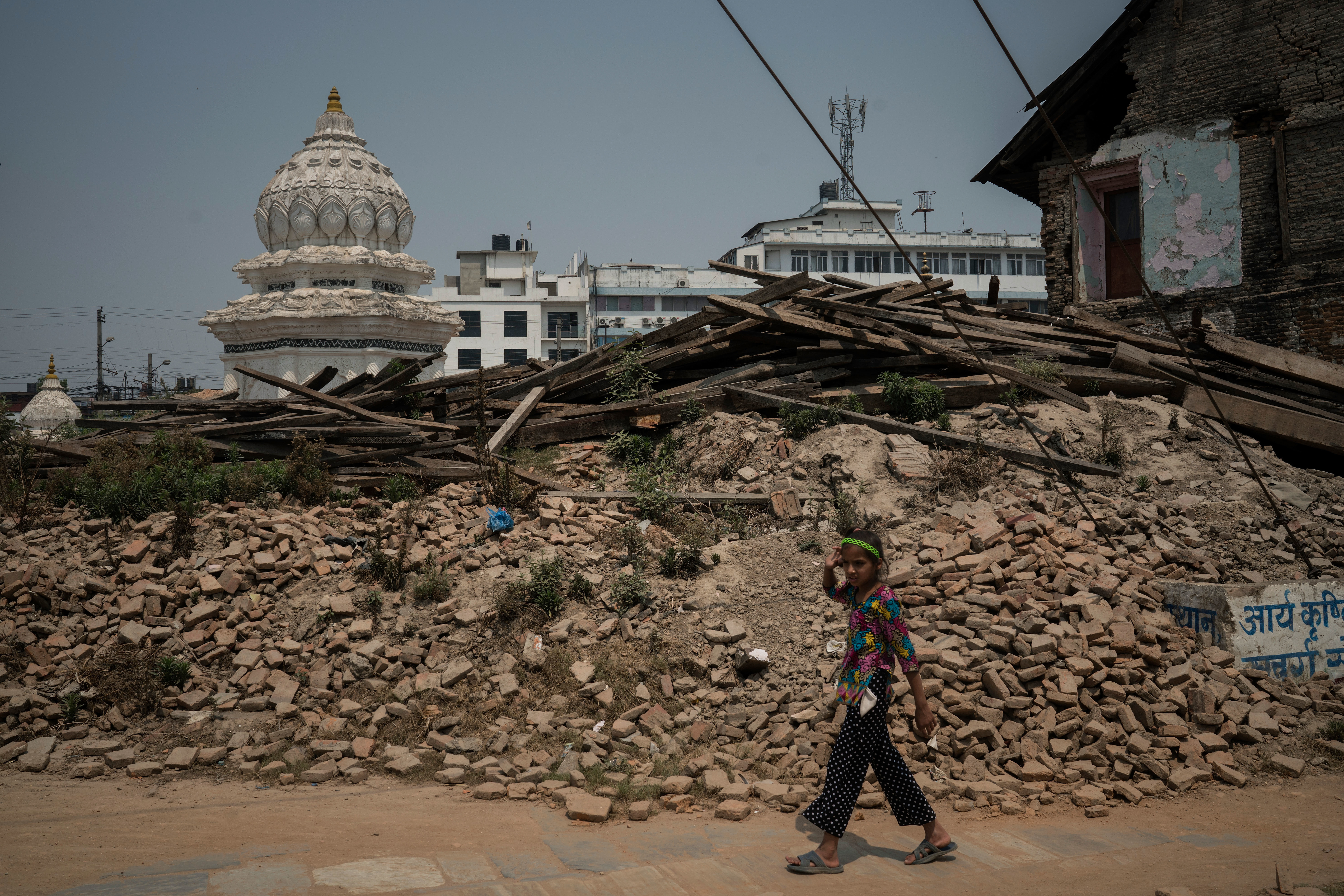A girl walks past the rubble of the Kalmochan Mahadev temple on April 25, 2016 in Kathmandu, Nepal. A 7.8-magnitude earthquake struck here on April 25, 2015. An estimated 9,000 people died.