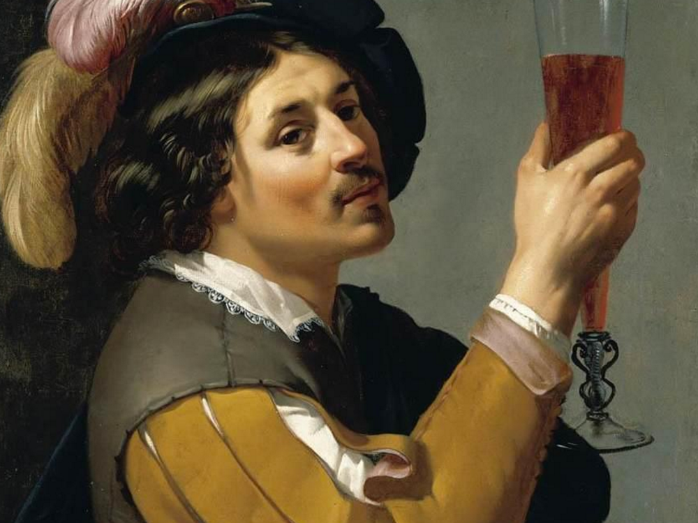 A young man drinking wine.
