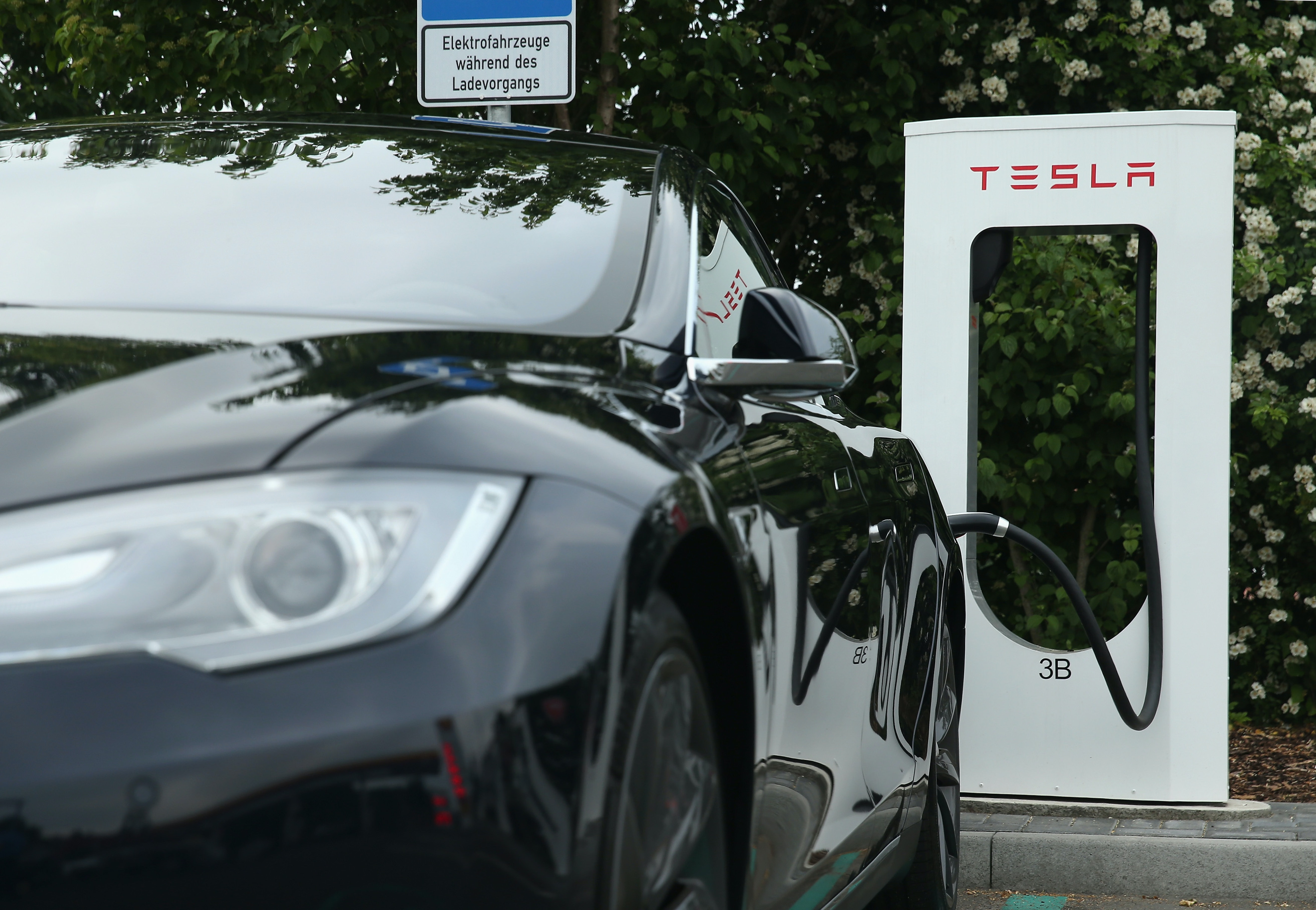 A Tesla electric-powered sedan stands at a Tesla charging station at a highway rest stop along the A7 highway on June 11, 2015 near Rieden, Germany.