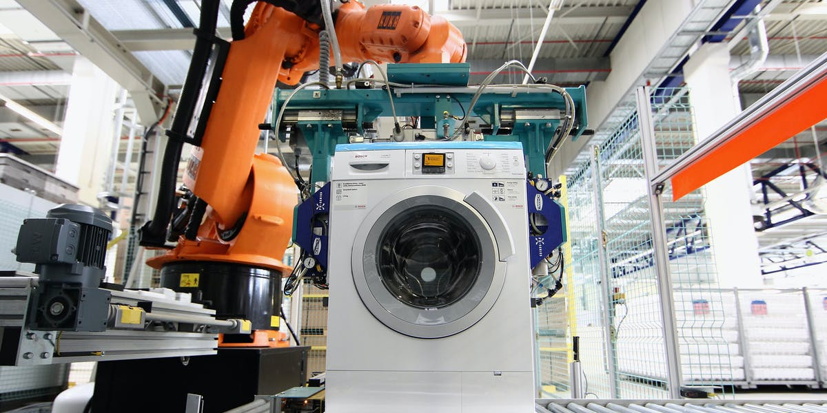 A robot assembles Washing Machines at the BSH Bosch Siemens Hausgeraetewerk Nauen consumer appliances factory, the world's third-largest appliance maker, in Nauen, Germany.
