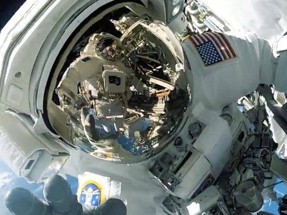 An astronaut waves to the camera as he records a spacewalk.