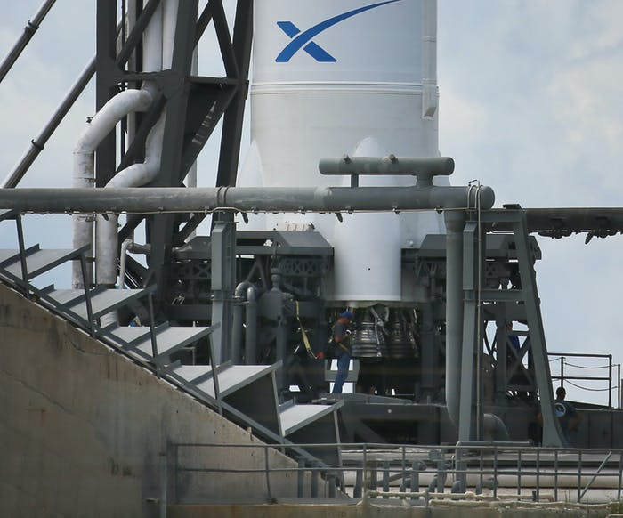 CAPE CANAVERAL, FL - OCTOBER 07: A worker is seen near the engines for the SpaceX Falcon 9 rocket attached to the cargo-only capsule called Dragon as it sits on the launch pad for a scheduled evening launch on October 7, 2012 in Cape Canaveral, Florida. The rocket will bring cargo to the International Space Station that consists of clothing, equipment and science experiments. (Photo by Joe Raedle/Getty Images)