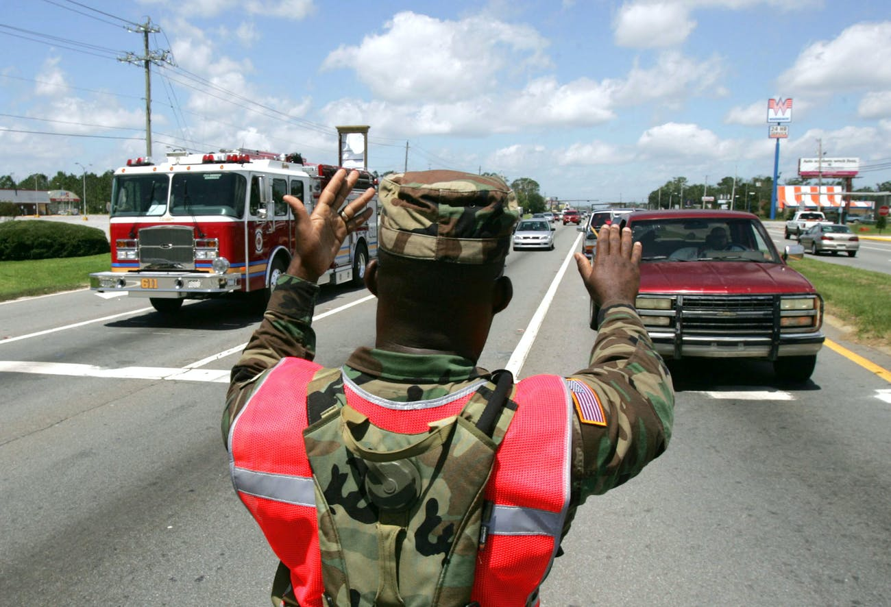 PENSACOLA, FL - JULY 11: US National Guardsman Sgt. Robert Gaines directs traffic July 11, 2005 in in Pensacola, Florida. He and other members of the 1st Battalion 265th ADA National Guard unit were activated to help with the recovery efforts from Hurricane Dennis. Traffic became congested as emergency vehicles and returning residents congested the cities roadways. (Photo by John Moore/Getty Images)