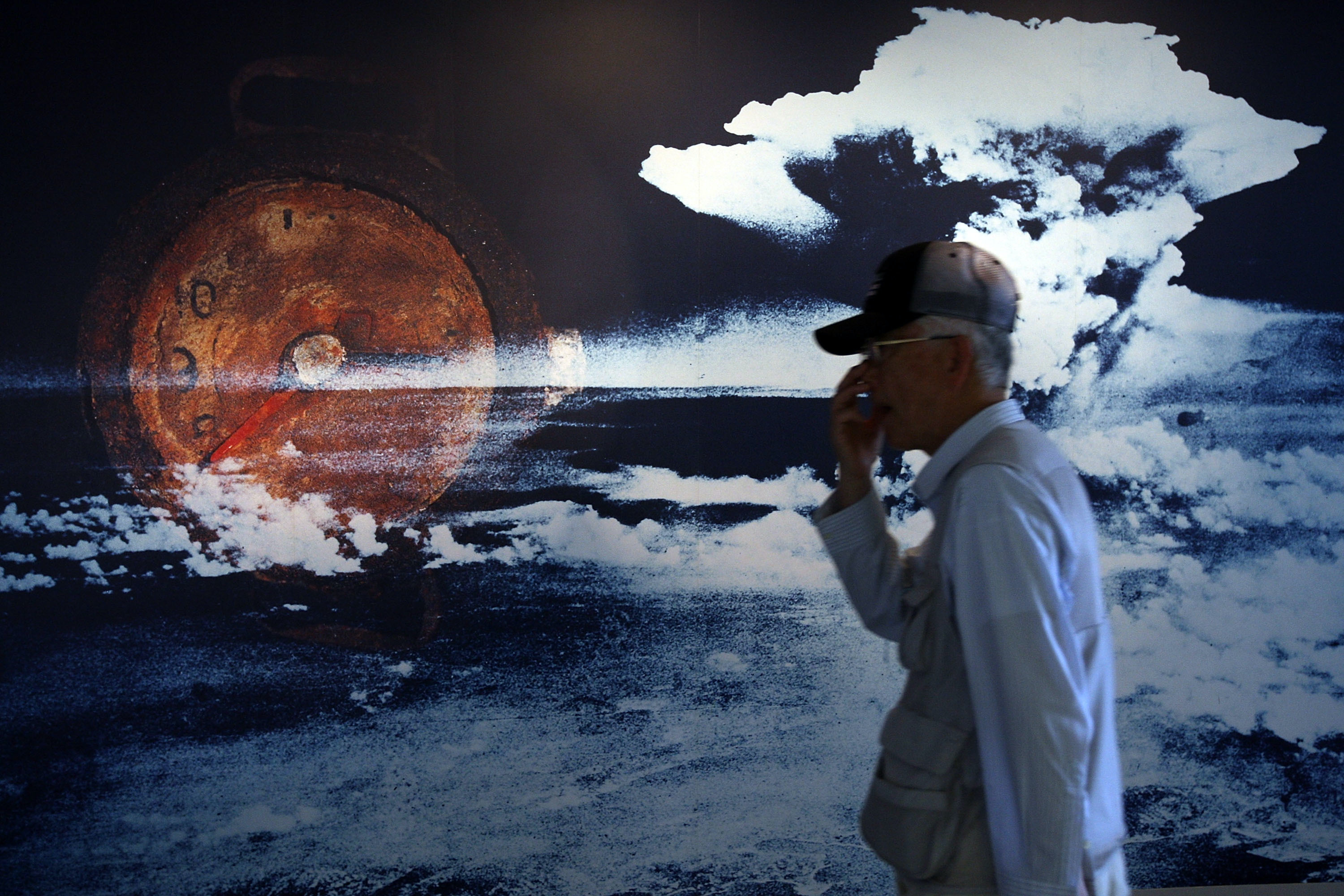 A visitor passes by a wall displaying a picture of the mushroom cloud when the atomic bomb was dropped over Hiroshima in 1945, at the Peace Memorial Museum in Japan.