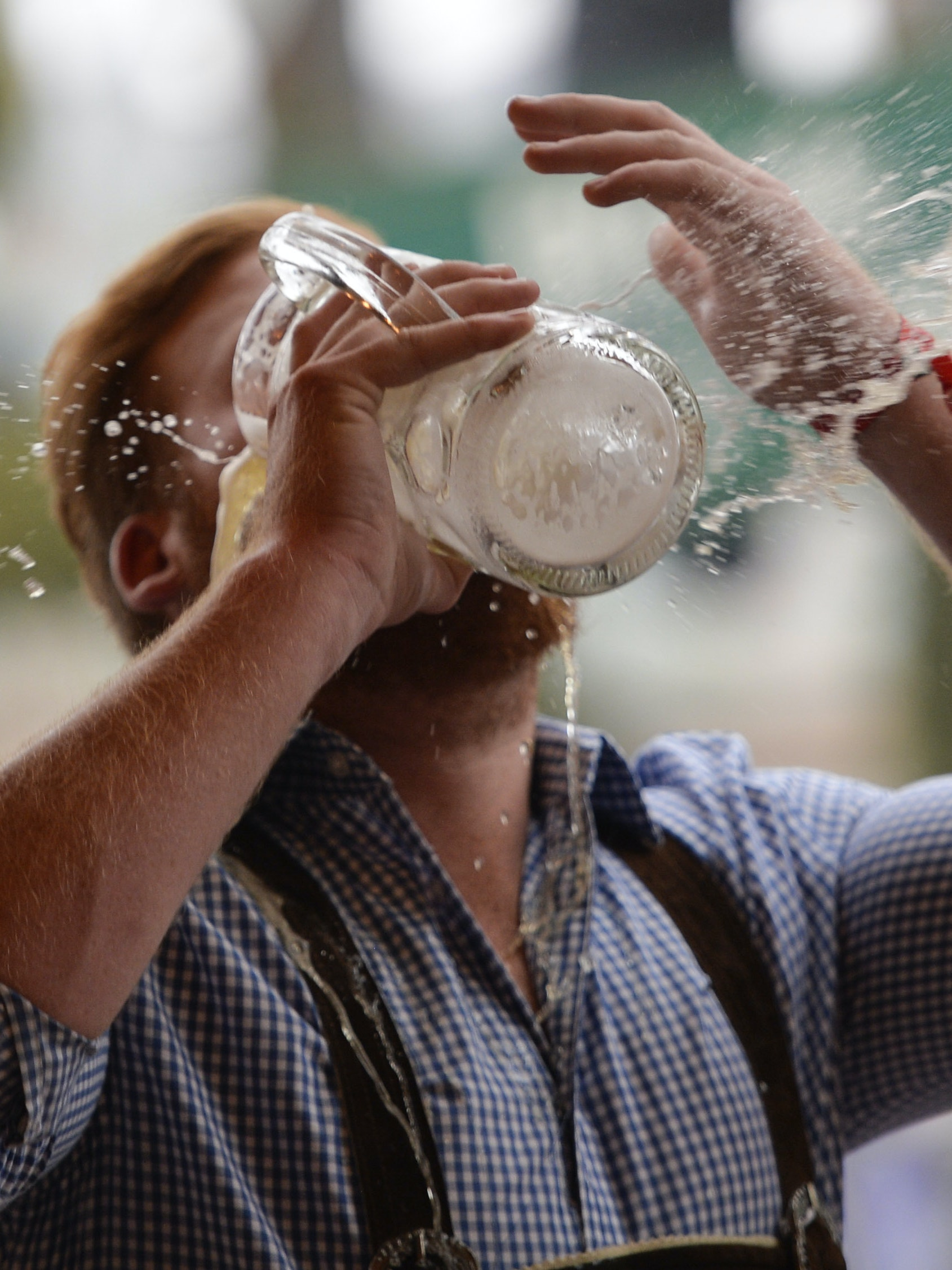 MUNICH, GERMANY - SEPTEMBER 19: A reveller spills beer as he tries to empty his stein in one sitting at the Hofbraeu tent on the opening day of the 2015 Oktoberfest on September 19, 2015 in Munich, Germany. The 182nd Oktoberfest will be open to the public from September 19 through October 4 and will draw millions of visitors from across the globe in the world's largest beer fest. (Photo by Philipp Guelland/Getty Images)