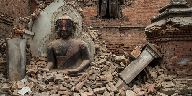 A Buddha statue is surrounded by debris from a collapsed temple in the UNESCO world heritage site of Bhaktapur on April 26, 2015 in Bhaktapur, Nepal. A major 7.8 earthquake hit Kathmandu mid-day on Saturday, and was followed by multiple aftershocks that triggered avalanches on Mt. Everest that buried mountain climbers in their base camps.