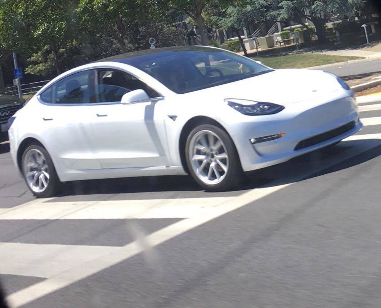 A white Model 3 out on the streets. Note the lip running across the doors.