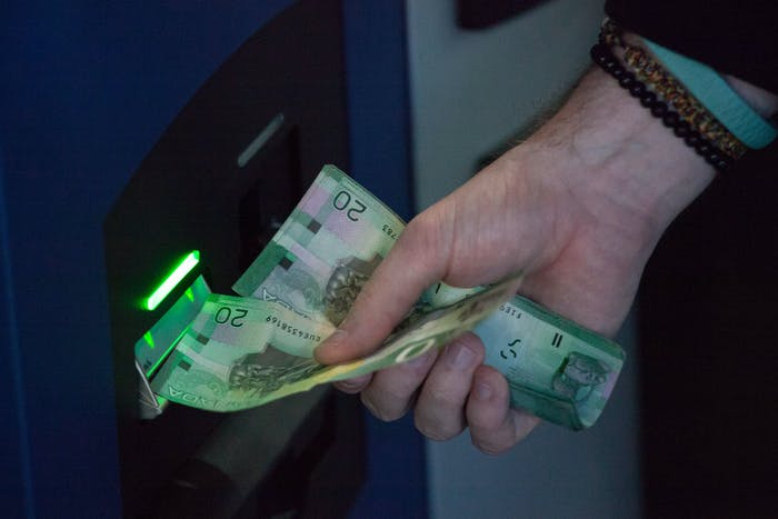 VANCOUVER, BC - OCTOBER 29: A user inserts Canadian currency into the world's first bitcoin ATM in exchange for bitcoins ATM at Waves Coffee House on October 29, 2013 in Vancouver, British Columbia, Canada. The ATM, named Robocoin, allows users to buy or sell the digital currency known as bitcoins. Once only used for black market sales on the internet, bitcoins are starting to be accepted at a growing number of businesses. (Photo by David Ryder/Getty Images)
