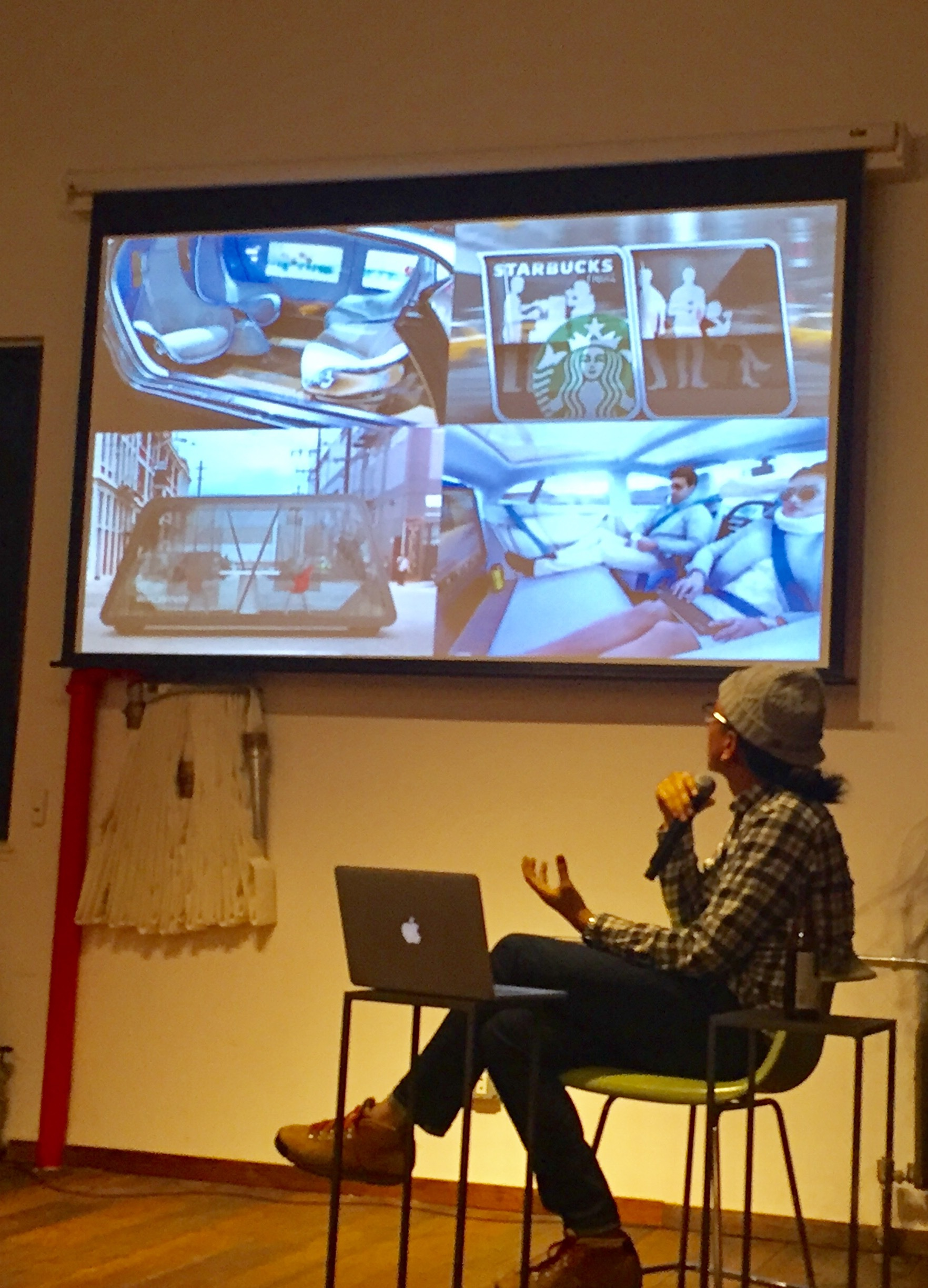 Kobayasha talking about different concept art for autonomous cars, from social spaces where the seats face each other, conference room cars, to futuristic lounge spaces.