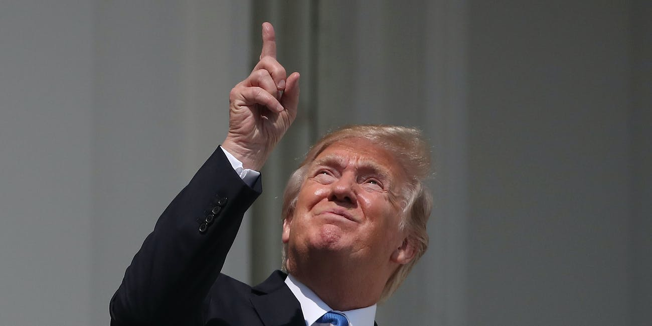 WASHINGTON, DC - AUGUST 21: U.S. President Donald Trump looks up toward the Solar Eclipse on the Truman Balcony at the White House on August 21, 2017 in Washington, DC. Millions of people have flocked to areas of the U.S. that are in the 'path of totality' in order to experience a total solar eclipse. (Photo by Mark Wilson/Getty Images)