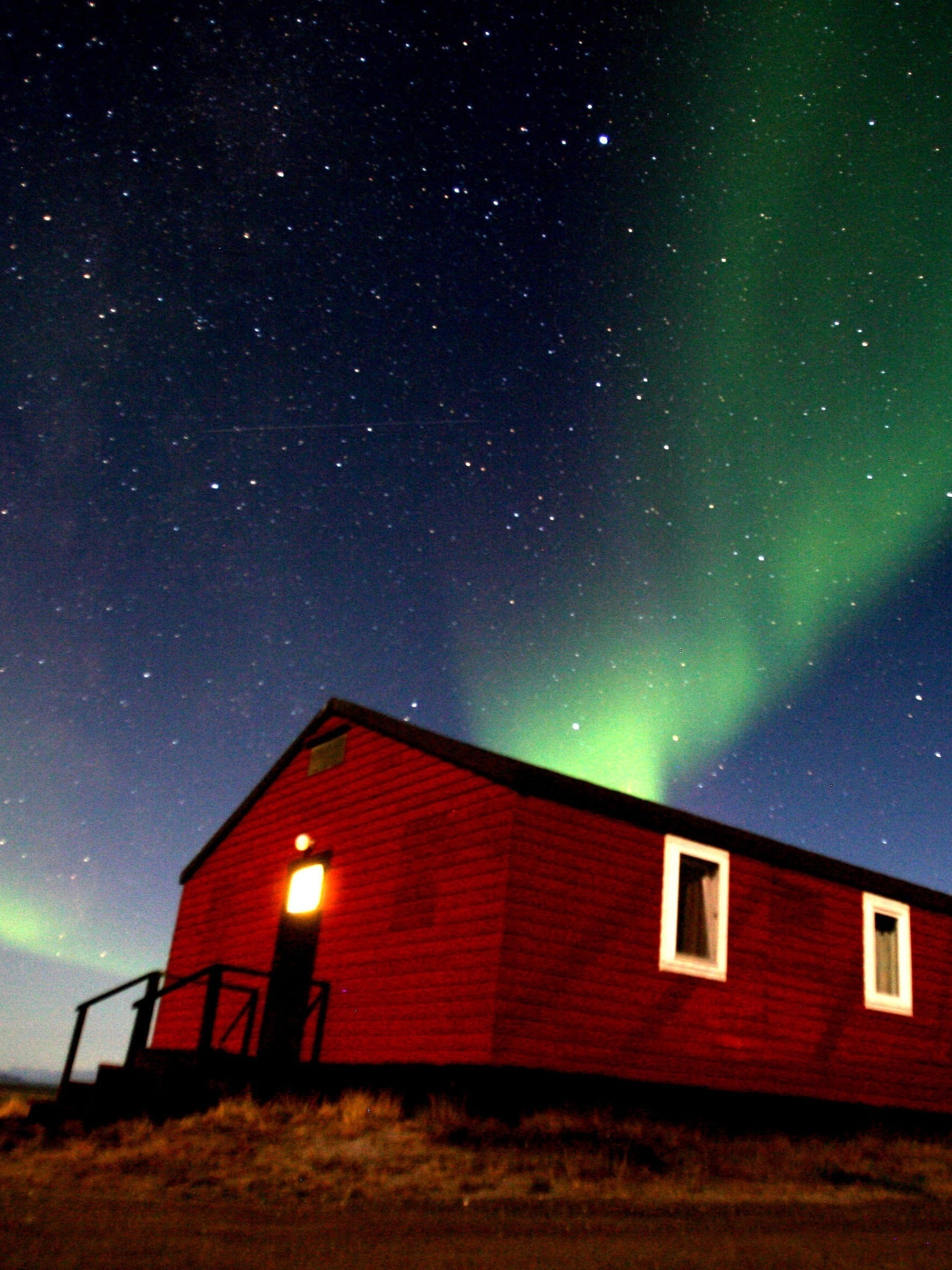 KANGERLUSSUAQ, GREENLAND - SEPTEMBER 03: (ISRAEL OUT) The Aurora Borealis glows in the sky, September 03, 2007, in the Greenland town of Kangerlussuaq. The Northern Lights most often occurs from September to October and from March to April and are a popular tourist attraction.  (Photo by Uriel Sinai/Getty Images)