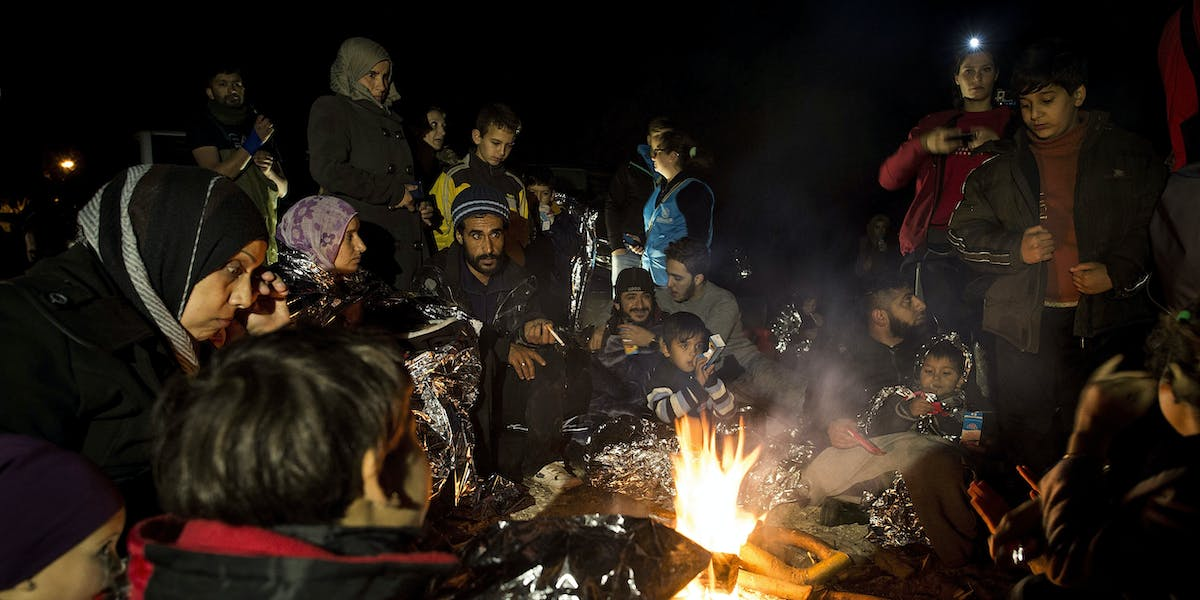 Refugees and migrants mainly from Afghanistan and Syria warm themselves after landing on a beach in Greece.