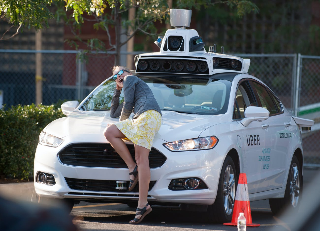 PITTSBURGH, PA - SEPTEMBER 22: A woman poses with an Uber driverless Ford Fusion as it sits in the Uber Technical Center parking lot on September, 22, 2016 in Pittsburgh, Pennsylvania. Uber has built its Uber Technical Center in Pittsburgh and is developing an autonomous vehicle that it hopes will be able to transport its millions of clients without the need for a driver. (Photo by Jeff Swensen/Getty Images)
