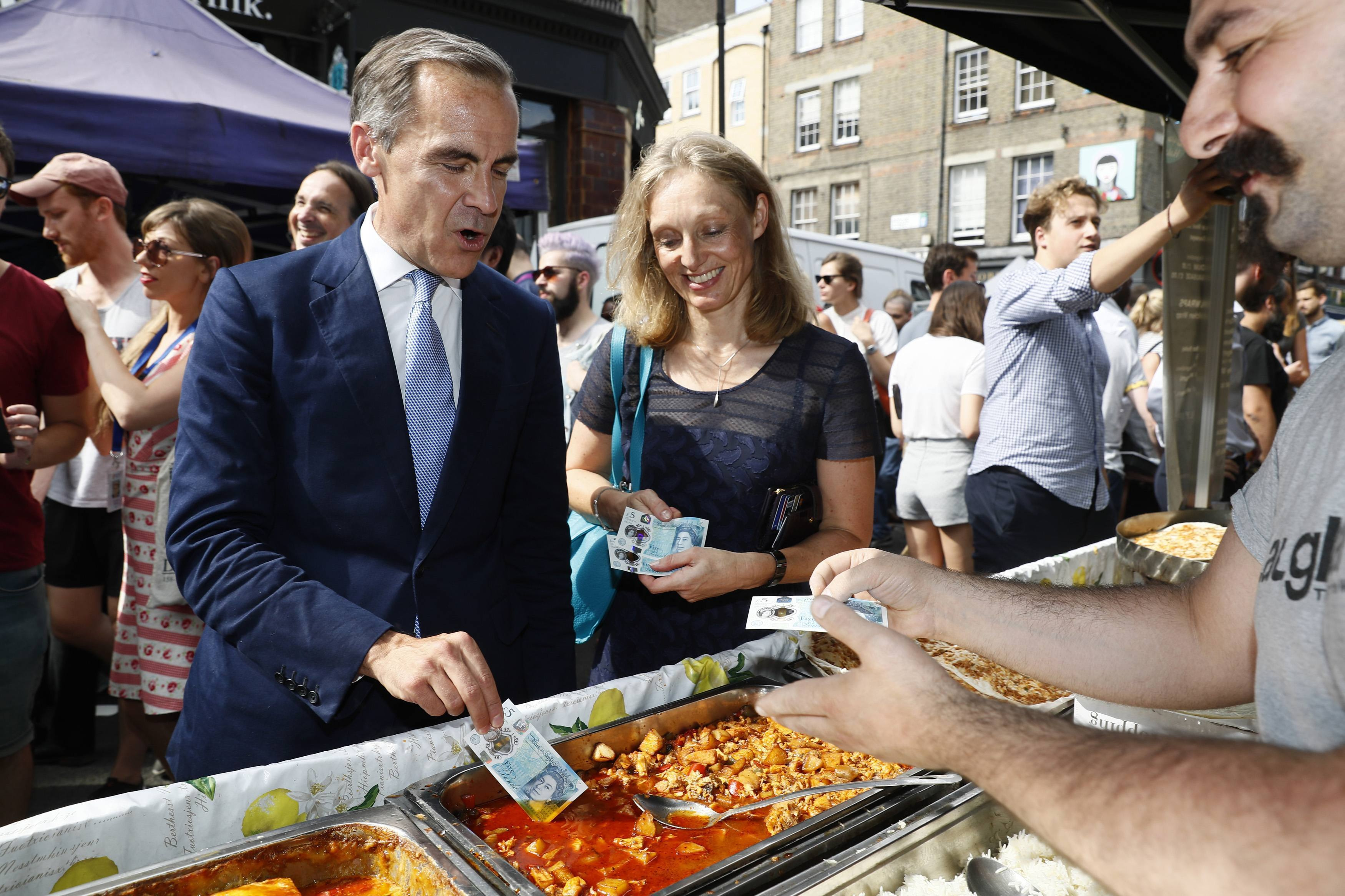 Bank of England governor Mark Carney tests a new polymer five pound note as he buys lunch at Whitecross Street Market.