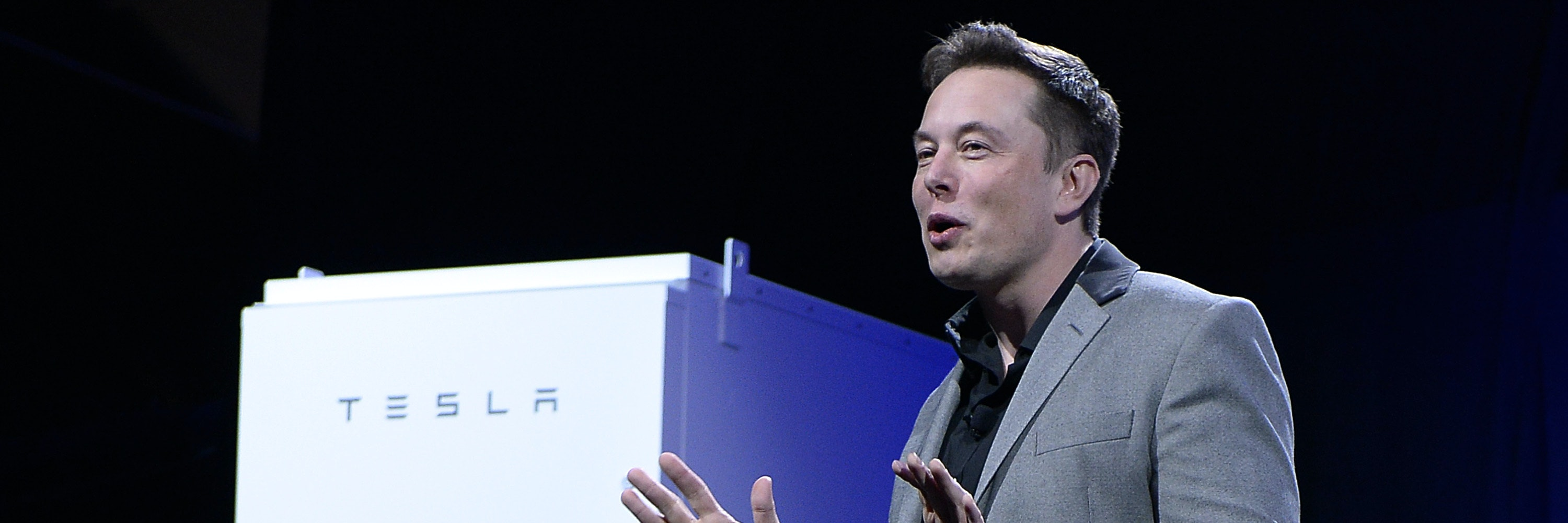 LOS ANGELES, CA - APRIL 30:  Elon Musk, CEO of Tesla, with a Powerpack unit the background unveils suit of batteries for homes, businesses, and utilities at Tesla Design Studio April 30, 2015 in Hawthorne, California. Musk unveiled the home battery named Powerwall with a selling price of $3500 for 10kWh and $3000 for 7kWh and very large utility pack called Powerpack. (Photo by Kevork Djansezian/Getty Images)