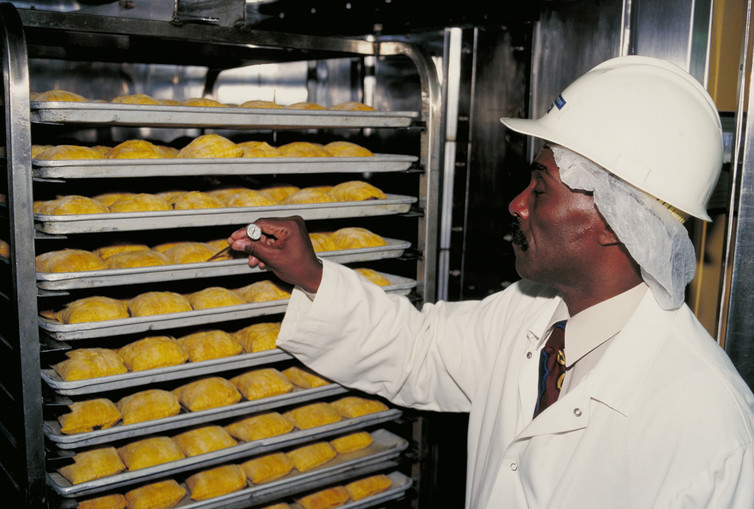 A U.S. Department of Agriculture inspector checks the temperature of Jamaican beef patties at various control points to prevent growth of pathogenic bacteria, as required by federal regulations.