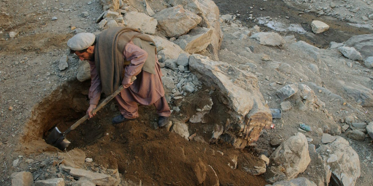 399010 07: An anti-Taliban fighter digs into a collapsed Al Qaeda cave December 26, 2001 deep in the Tora Bora valley of Afghanistan. The cave was collapsed by American bombings and is about a three hour hike from the nearest roads. The search continues in Tora Bora for Osama bin Laden. (Photo by Chris Hondros/Getty Images)
