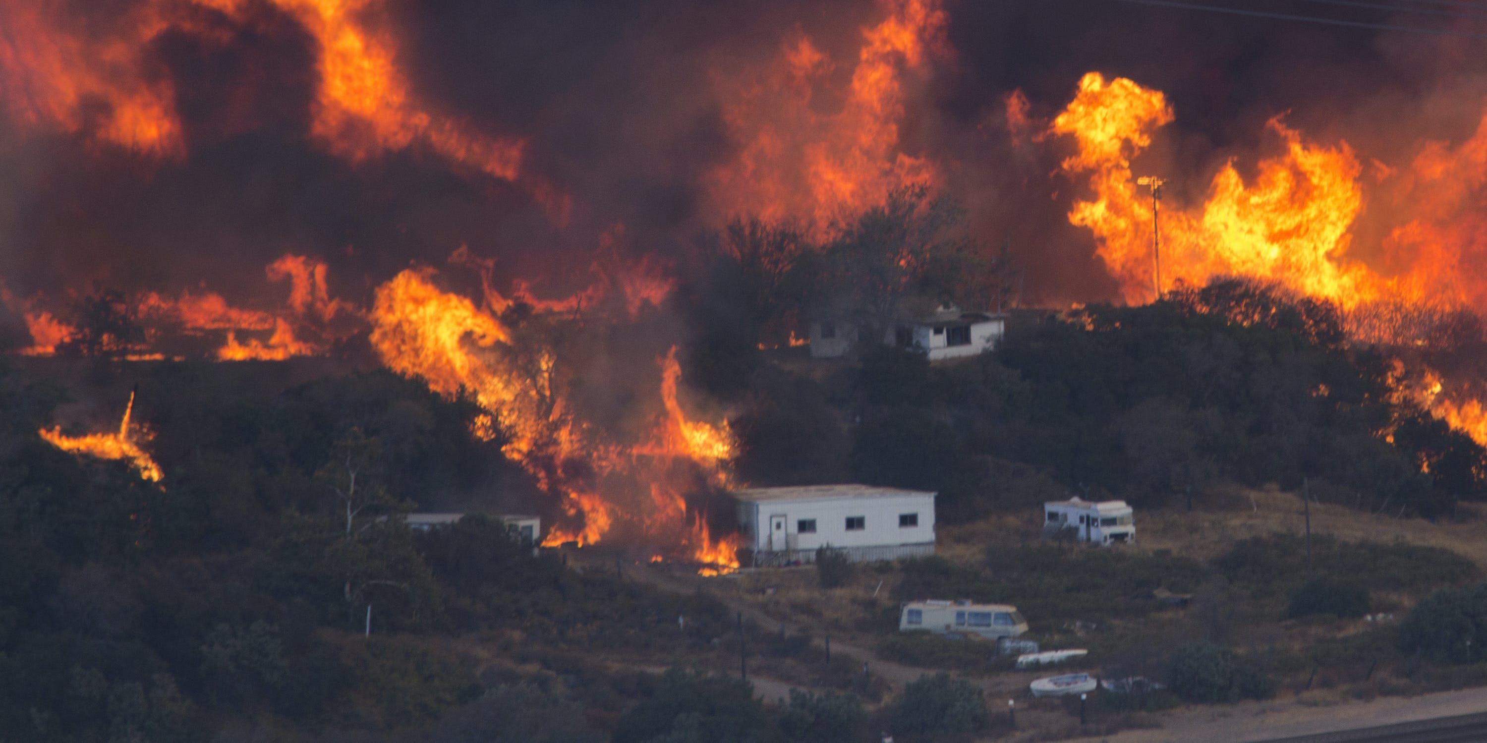 Flames sweep through a rural community at the Blue Cut Fire on August 17, 2016 near Wrightwood, California.. An unknown number of homes and businesses have burned and more than 80,000 people are under evacuation orders as the out-of-control wildfire spread beyond 30,000 acres and threatens to expand into the ski resort town of Wrightwood.